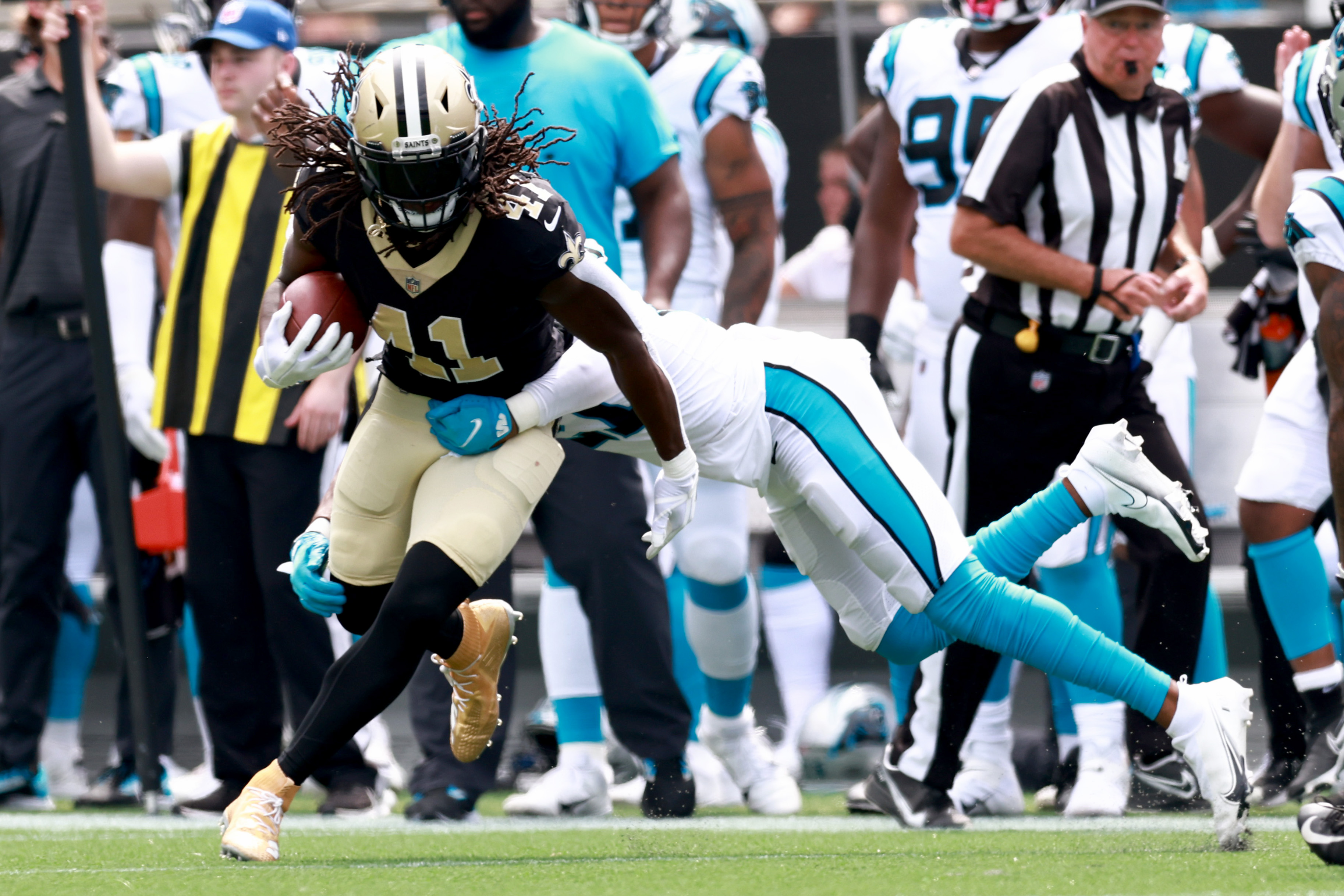 Running back Alvin Kamara #41 of the New Orleans Saints runs the ball during the first half in the game against the Carolina Panthers at Bank of America Stadium on September 19, 2021 in Charlotte, North Carolina.