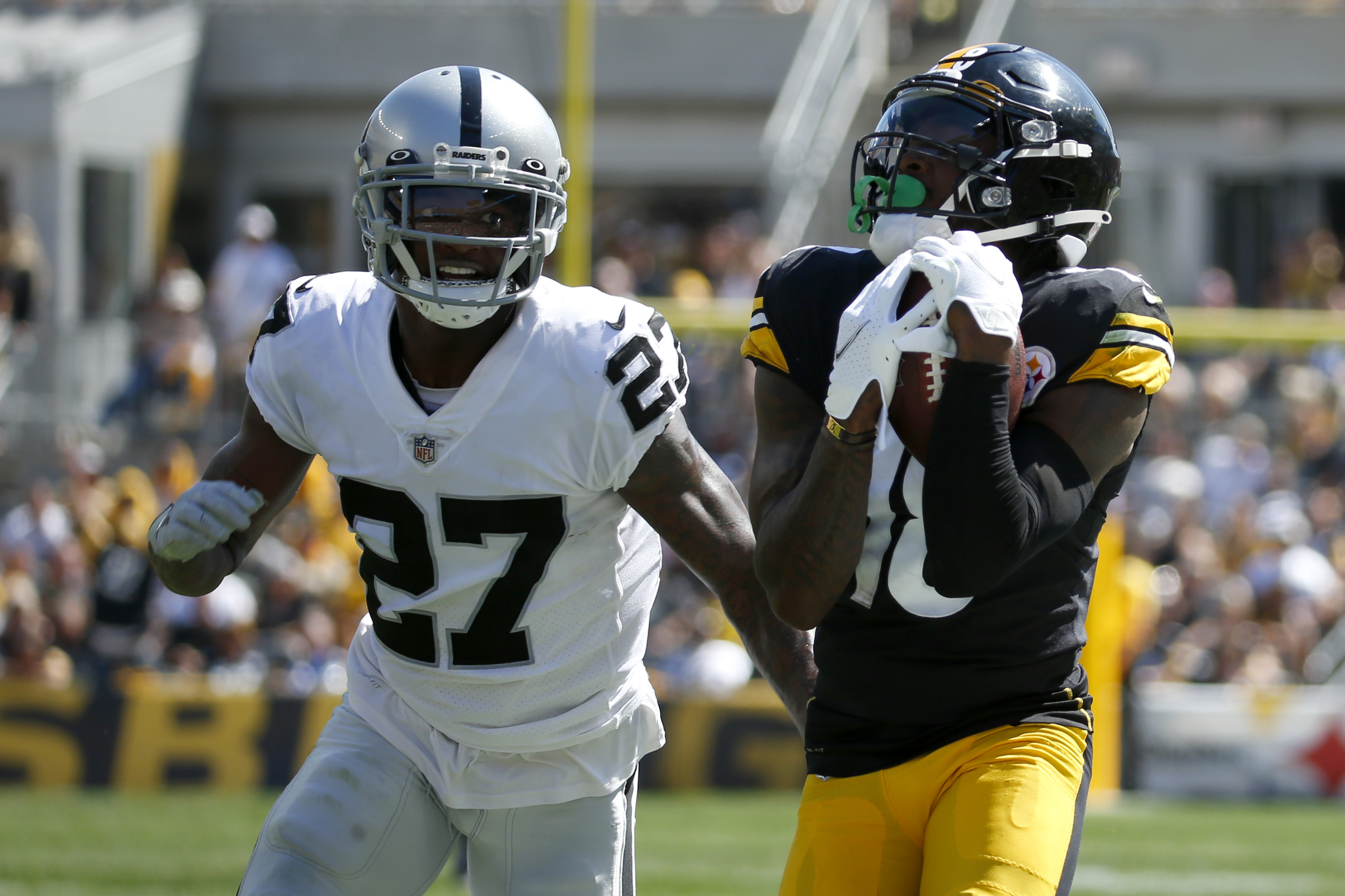 Wide receiver Diontae Johnson #18 of the Pittsburgh Steelers makes a catch against cornerback Trayvon Mullen Jr. #27 of the Las Vegas Raiders in the first quarter of the game at Heinz Field on September 19, 2021 in Pittsburgh, Pennsylvania.