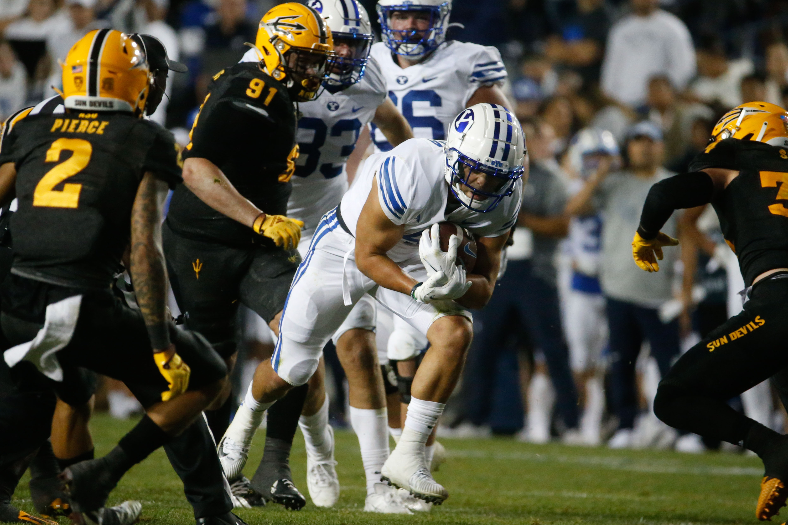 Brigham Young running back Lopini Katoa, center, runs under pressure during an NCAA college football game against Arizona State.