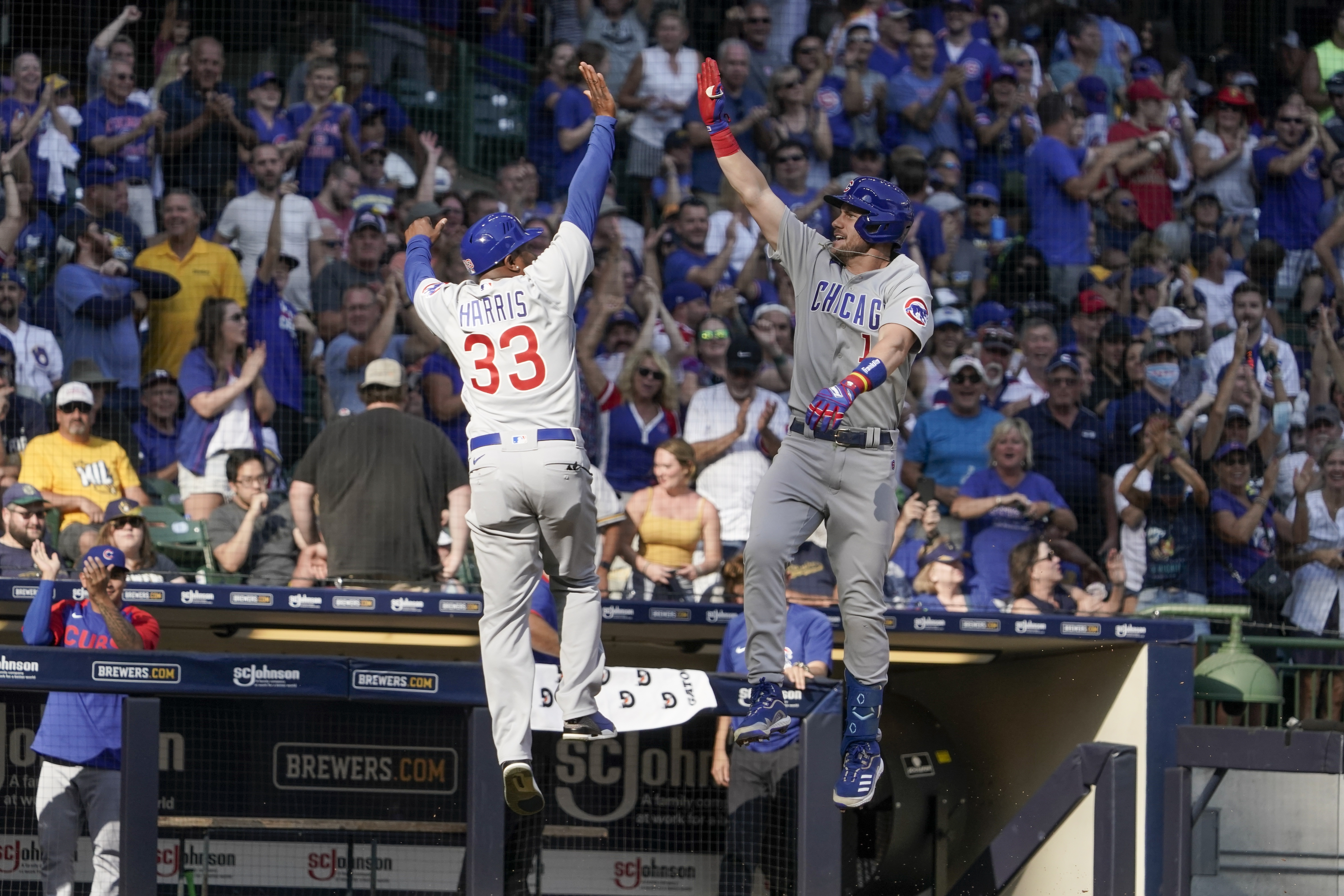 The Cubs' Patrick Wisdom celebrates with third base coach Willie Harris after hitting a three-run homer against the Milwaukee Brewers on Sunday.