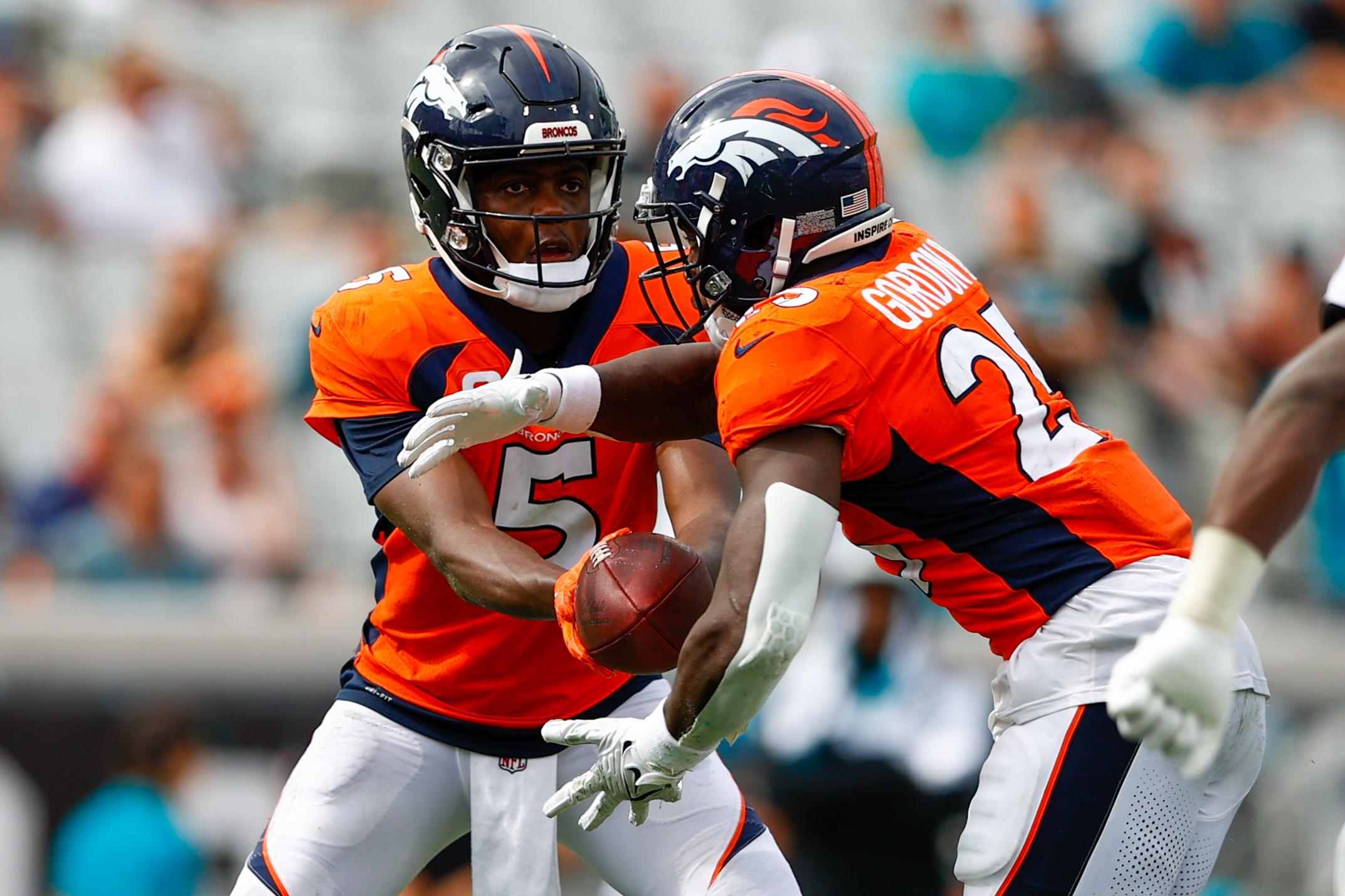 Denver Broncos quarterback Teddy Bridgewater (5) hands off to running back Melvin Gordon (25) in the fourth quarter at TIAA Bank Field.
