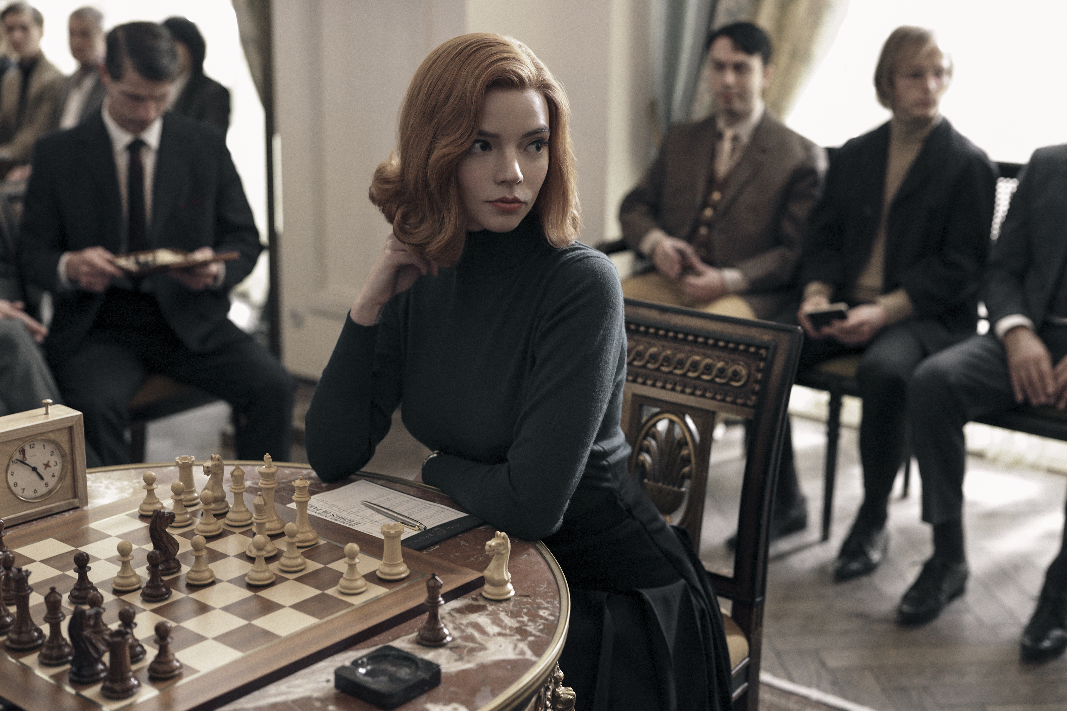 Queen's Gambit: girl sits at chess board