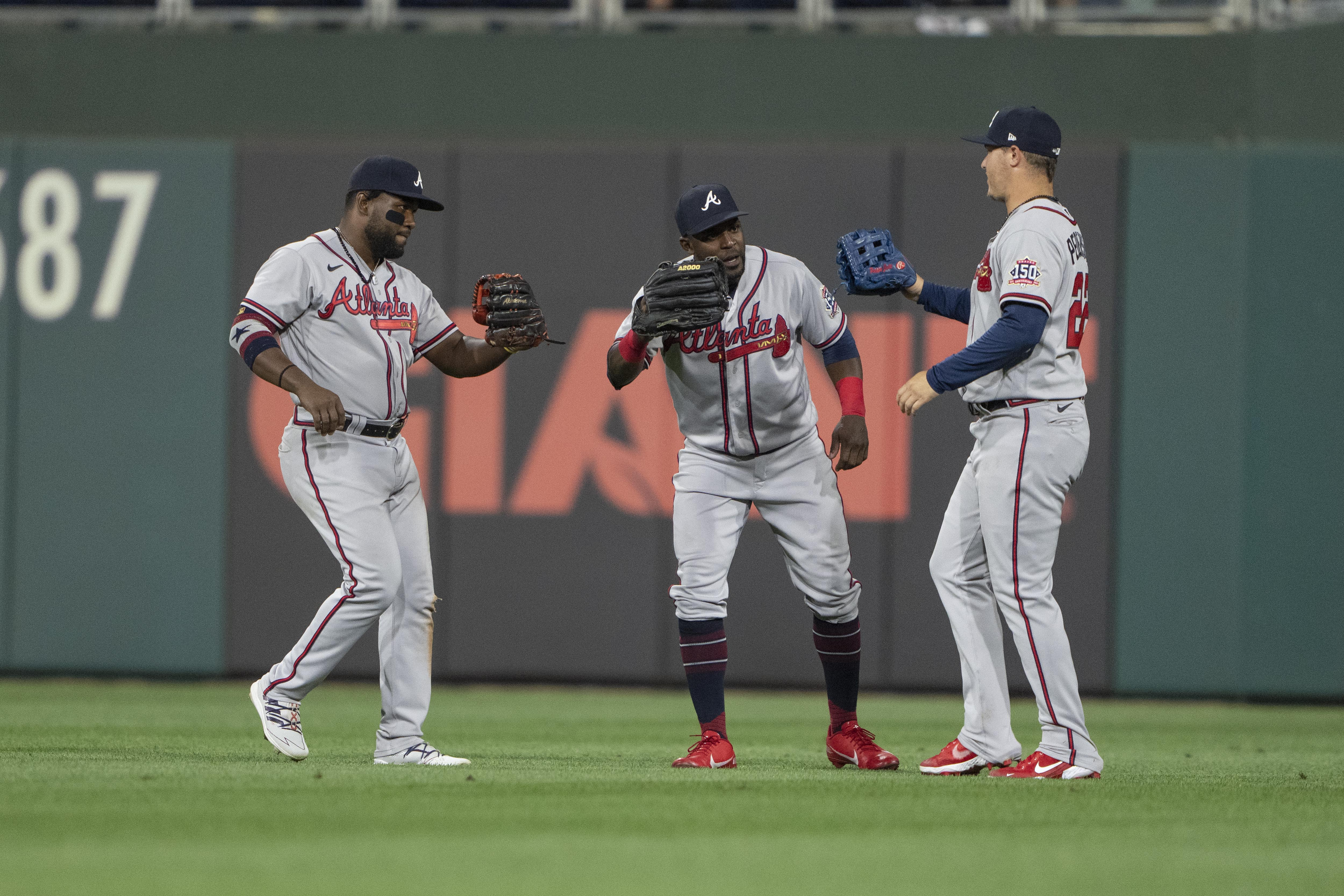 Atlanta Braves Left Fielder Abraham Almonte (34) and Atlanta Braves Center Fielder Guillermo Heredia (38) and Atlanta Braves Right Fielder Joc Pederson (22) celebrate the victory after the ninth inning of a Major League Baseball game between the Atlanta Braves and the Philadelphia Phillies on July 24, 2021, at Citizens Bank Park in Philadelphia, PA.