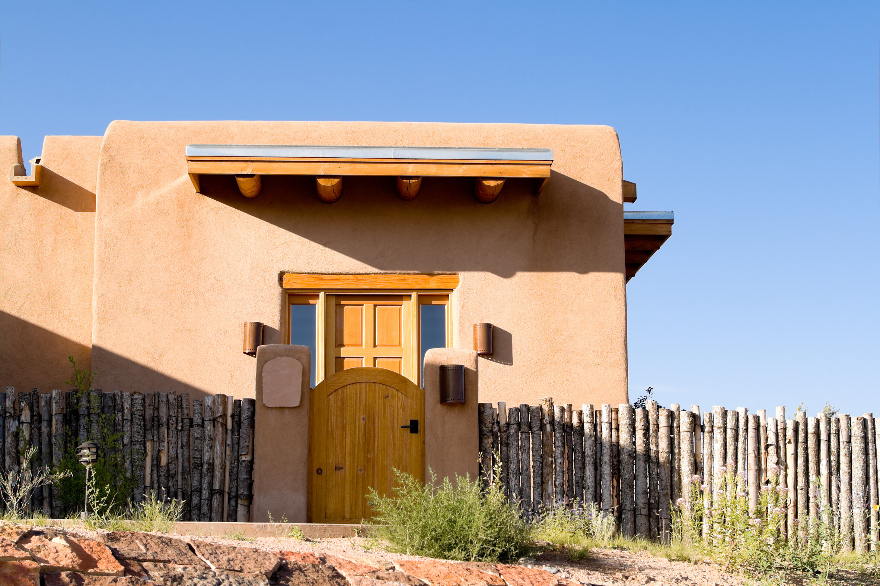 An Adobe style home with wood-log fence and wooden front door.