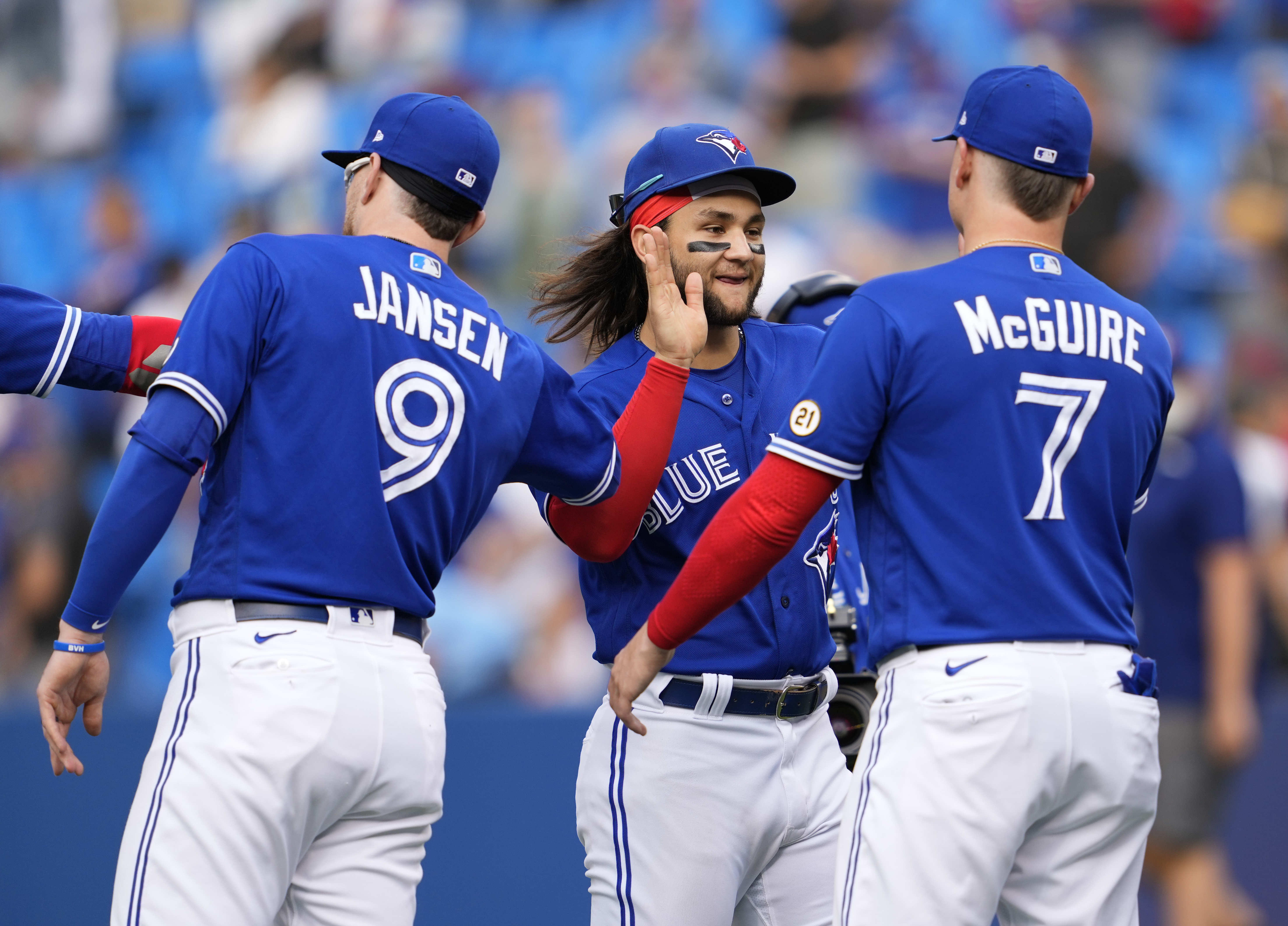 Bo Bichette, Reese McGuire, and Danny Jansen of the Toronto Blue Jays celebrate defeating the Tampa Bay Rays during their MLB game at the Rogers Centre on September 15, 2021 in Toronto, Ontario, Canada.