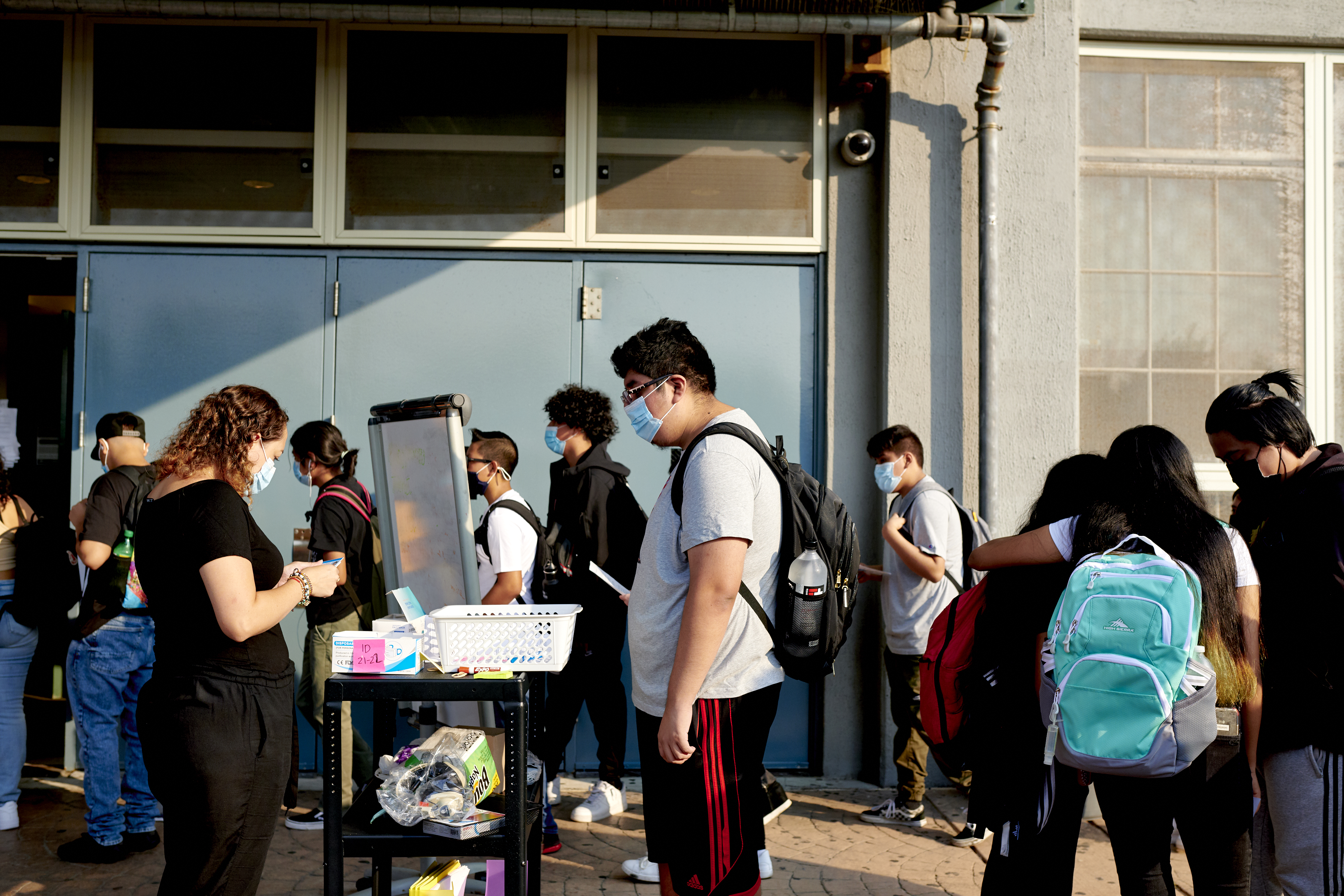Students wait for COVID screening forms outside of the entrance of their school.