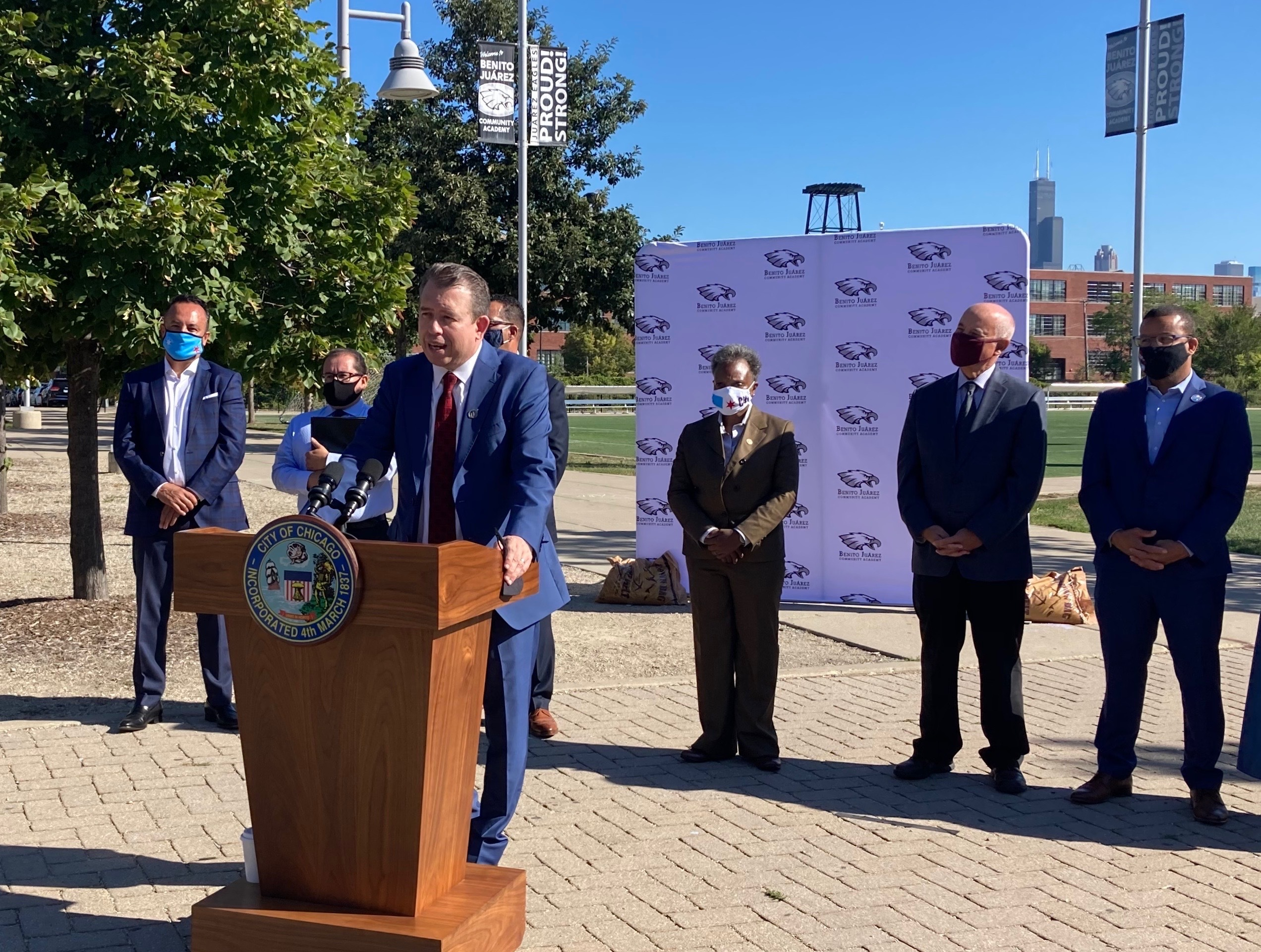 Newly announced Chicago Public Schools CEO Pedro Martinez, wearing a blue suit, stands outside at a lectern and speaks during a press conference as district leaders look on behind him.