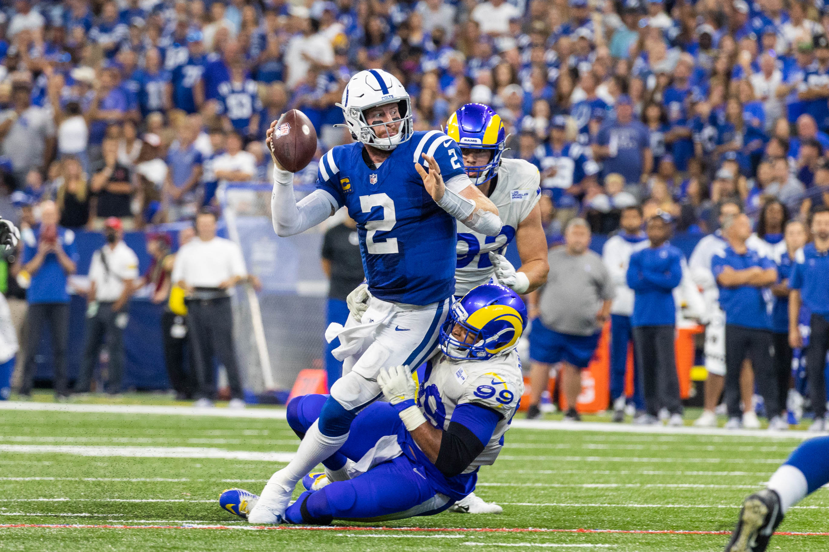 Indianapolis Colts quarterback Carson Wentz (2) passes the ball while Los Angeles Rams defensive end Aaron Donald (99) defends in the second half at Lucas Oil Stadium.