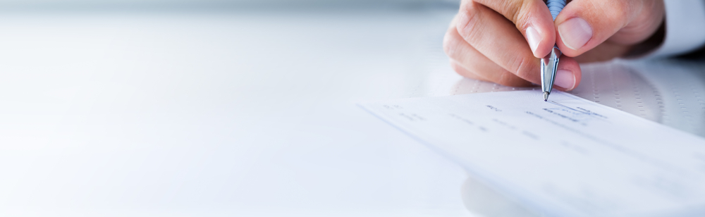 A hand uses a pen to fill out a business application