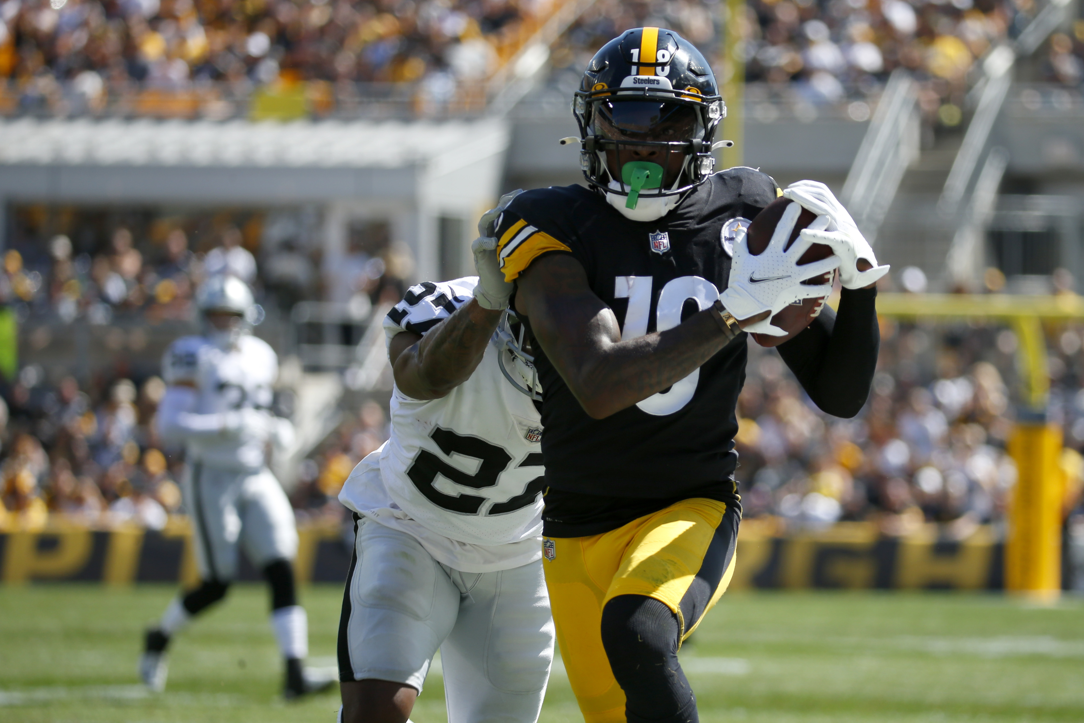 Wide receiver Diontae Johnson #18 of the Pittsburgh Steelers makes a catch against cornerback Trayvon Mullen Jr. #27 of the Las Vegas Raiders in the first half of the game at Heinz Field on September 19, 2021 in Pittsburgh, Pennsylvania.