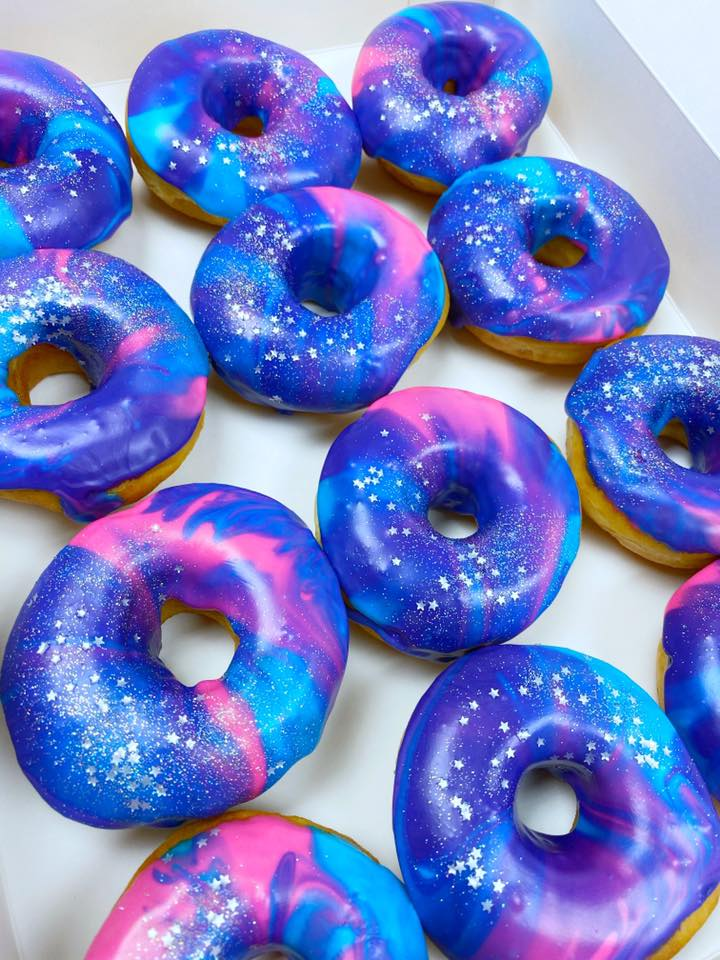 a dozen bright blue donuts glazed to look like a galaxy, with swirls of lighter blue and purple icing and edible star glitter