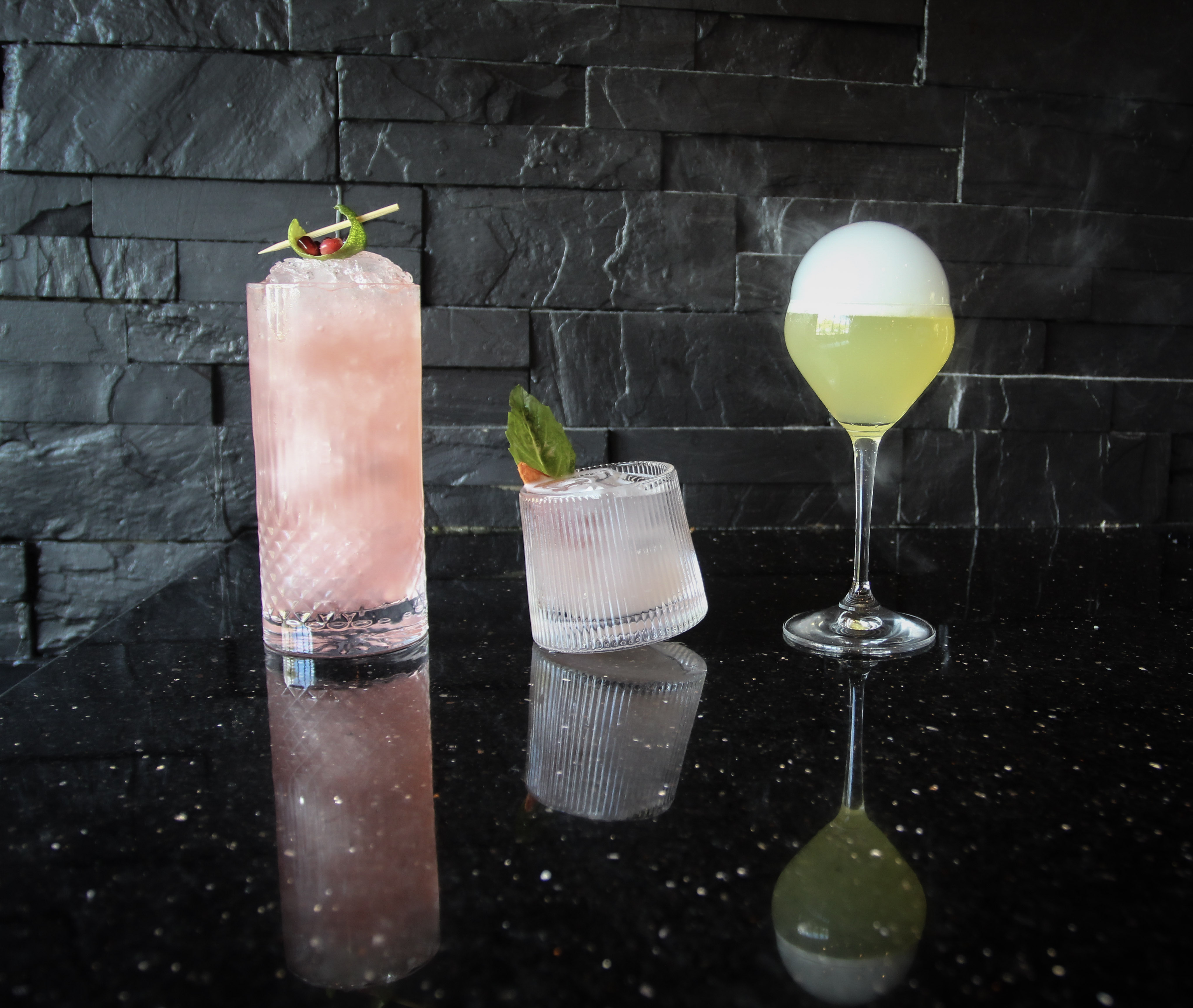 Three cocktails — one pink, one lighter pink, and one electric lime green —sit atop a black table, and are backdropped by a black wall.