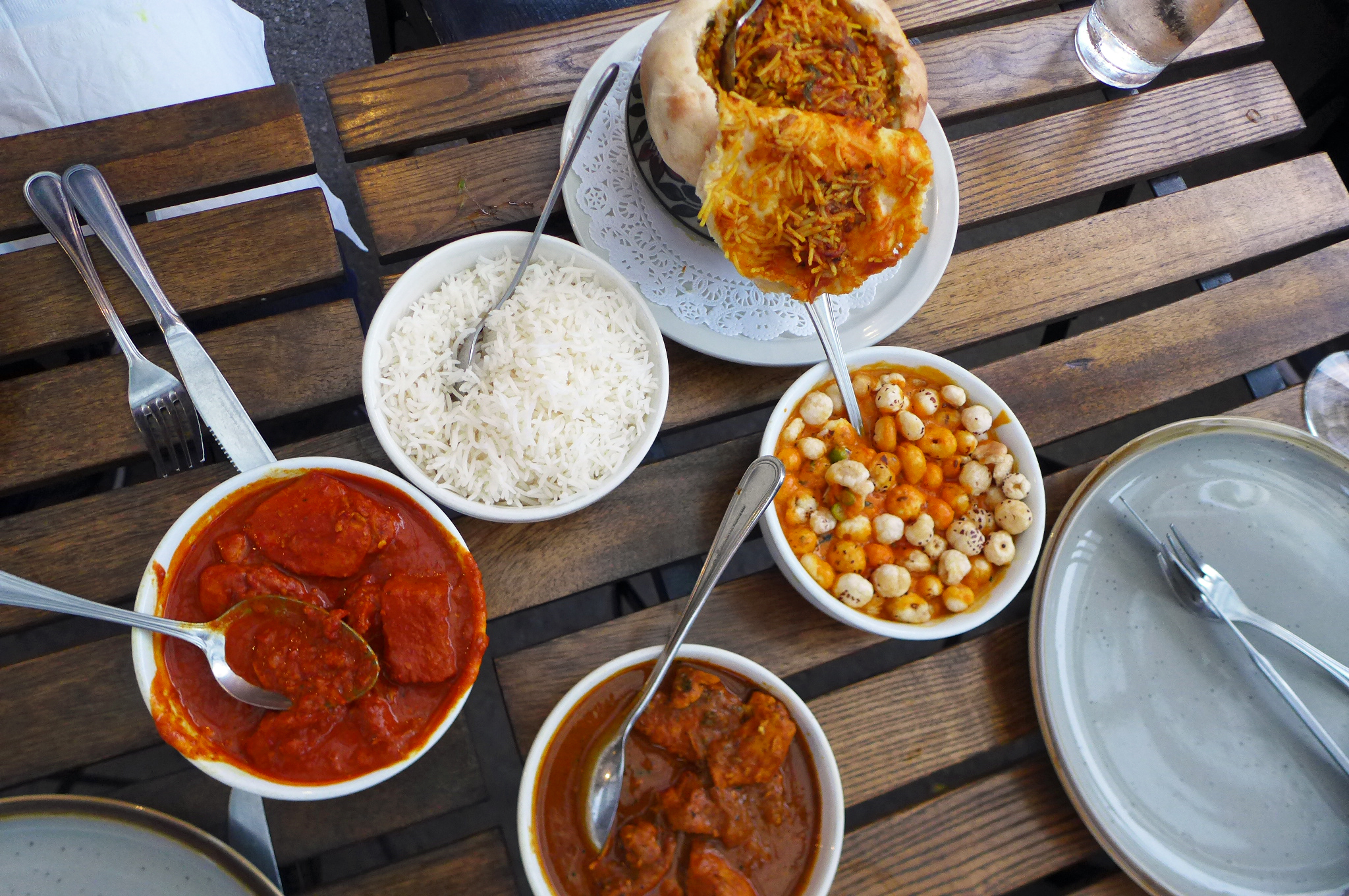 Three bowls of curry, one pie with top pulled back, and rice here and there.