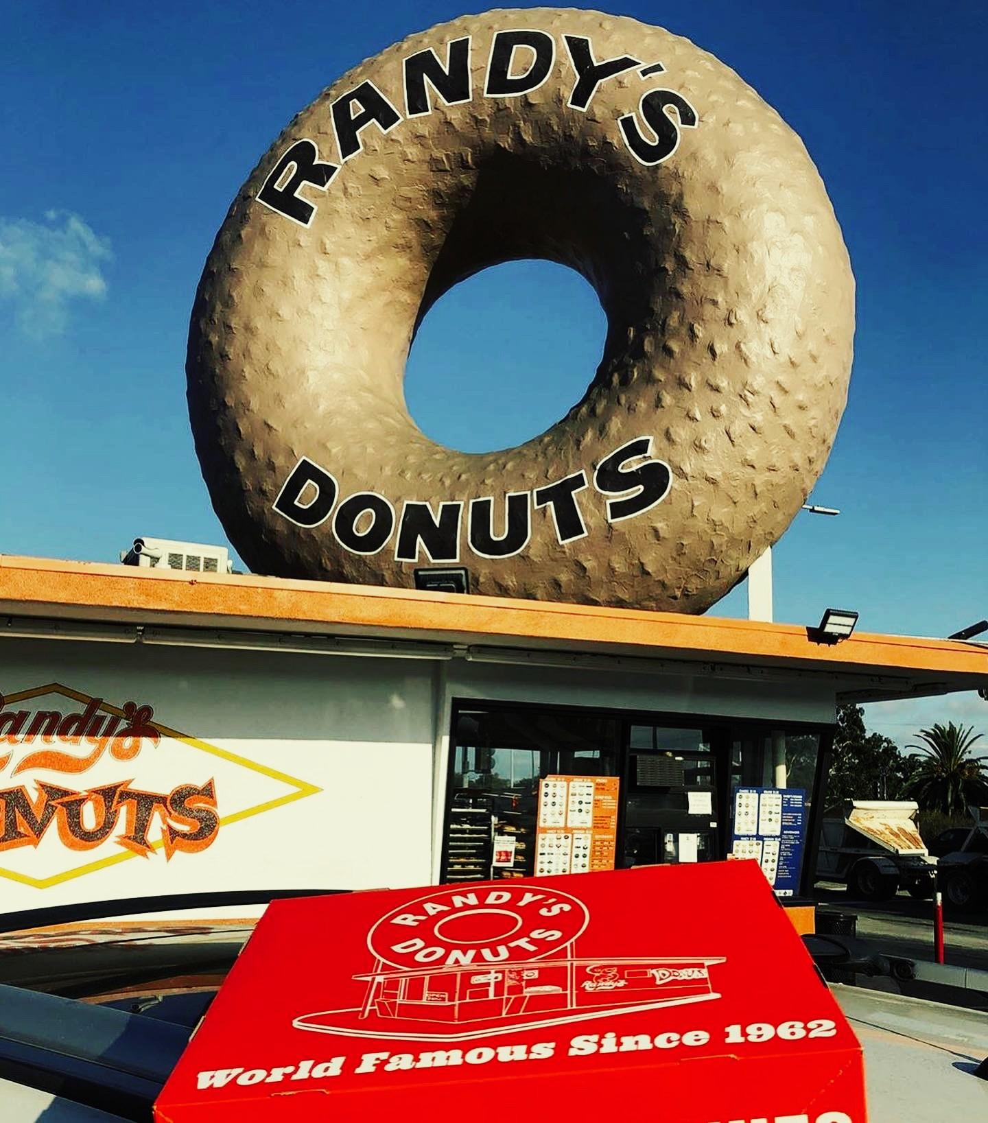 The exterior of a doughnut shop with a giant doughnut on top.