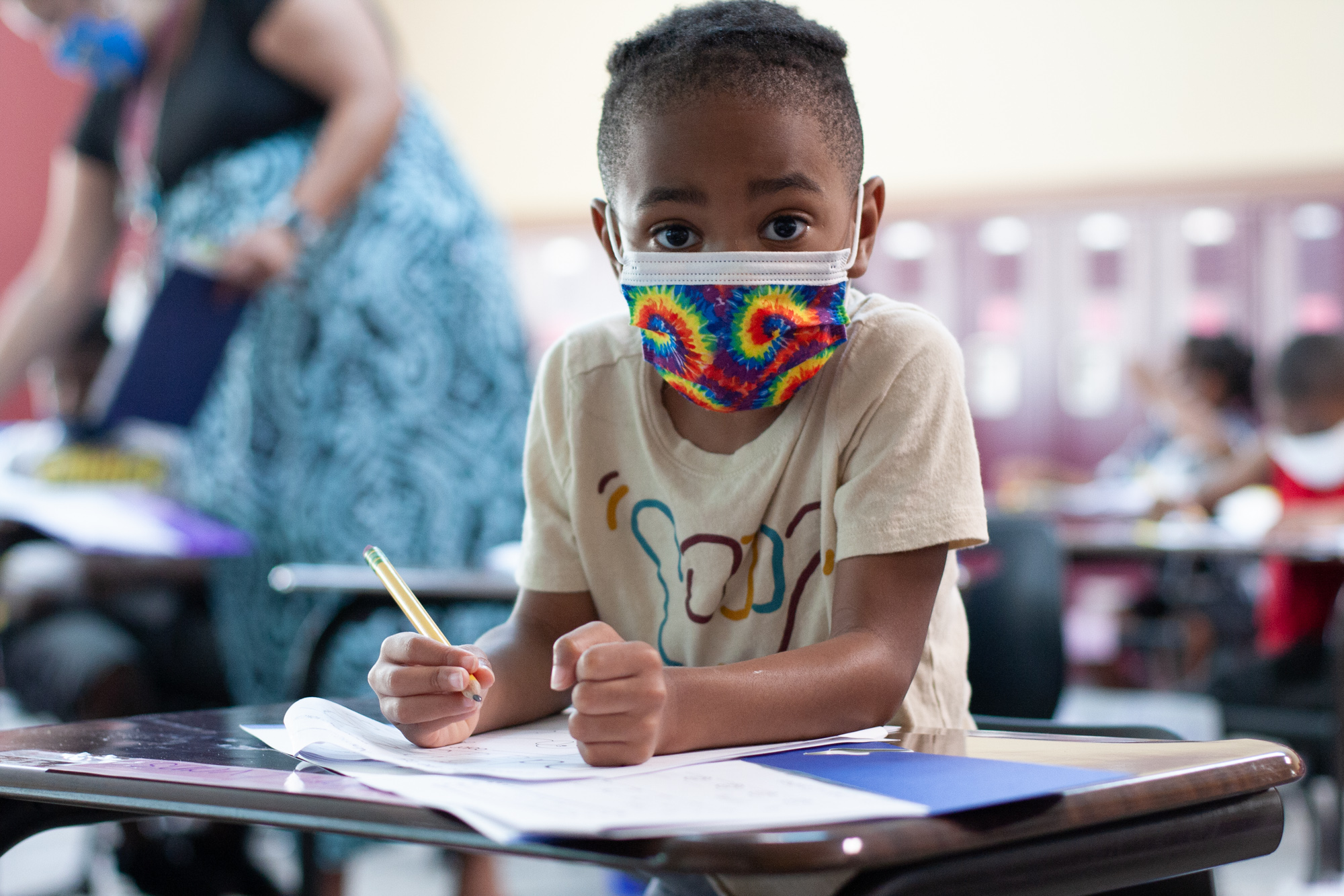 A young boy in a beige shirt with a tie-dye mask looks up at the camera in the middle of writing on a worksheet with a pencil as a teacher helps a student in the background
