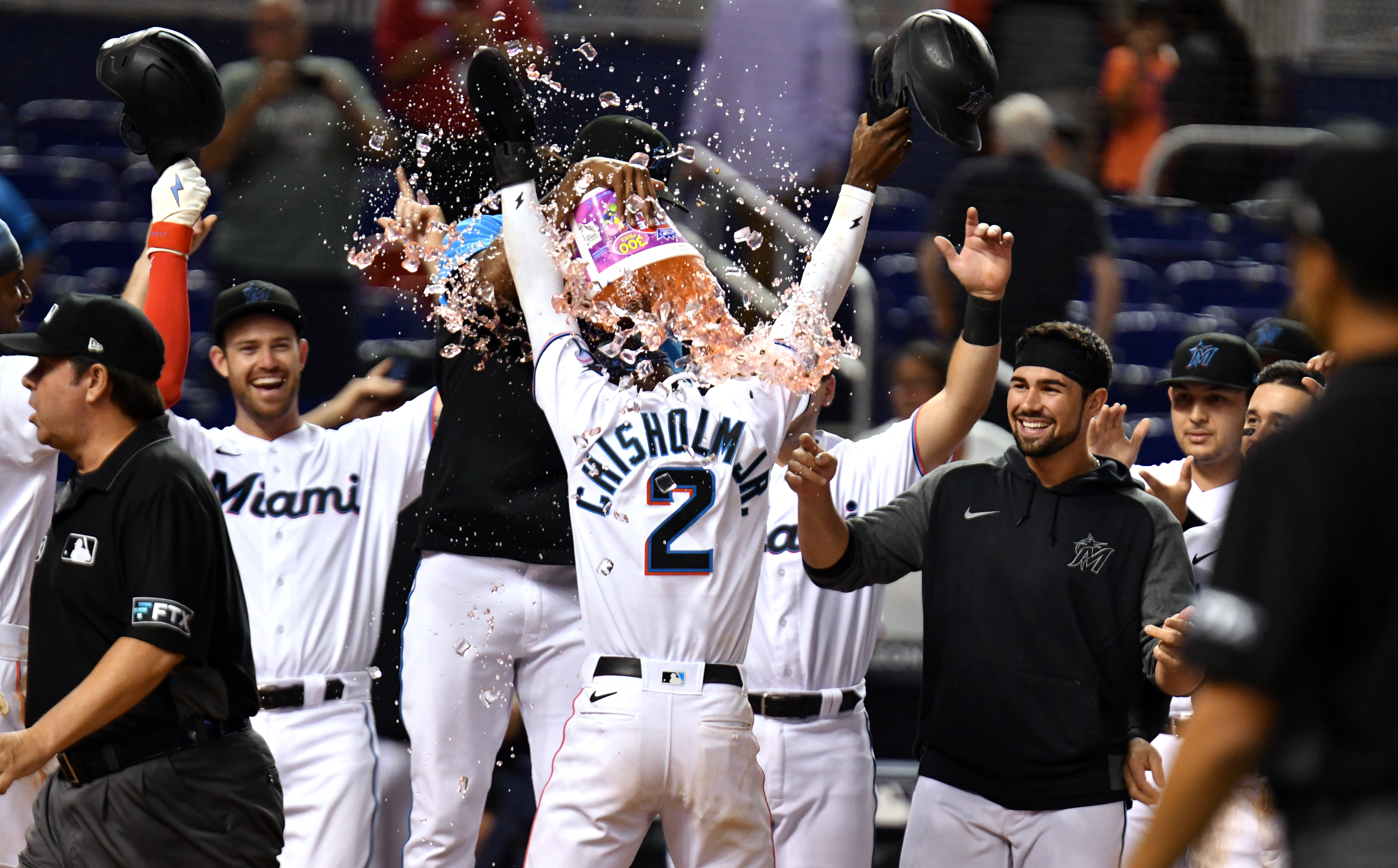 Miami Marlins second baseman Jazz Chisholm Jr. (2) celebrates with teammates scoring the winning run in the 10th inning against the Washington Nationals at loanDepot Park
