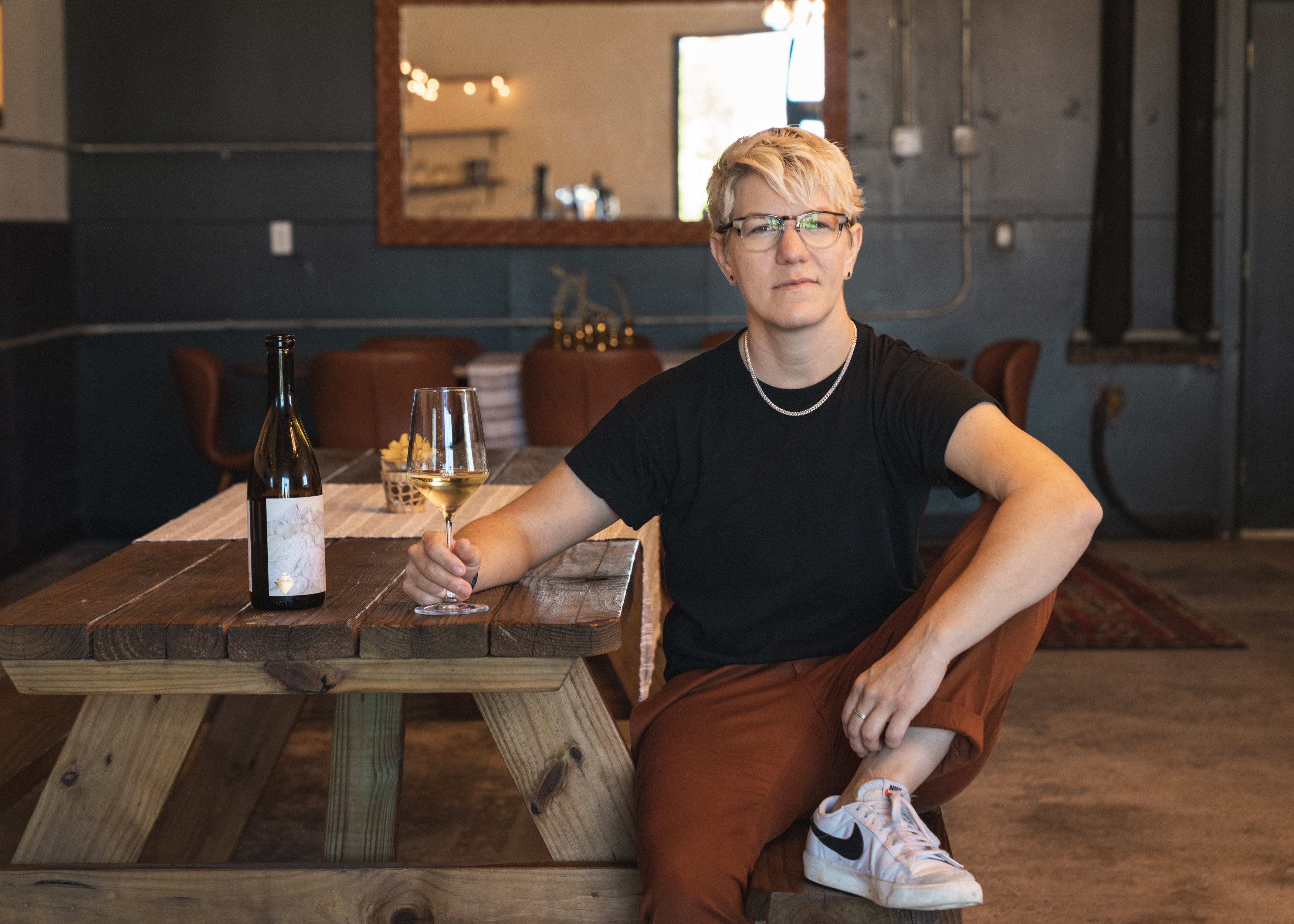 A woman with short blonde hair wearing a black T-shirt and brown pants sitting at an indoor picnic table with one foot on the seat, while holding a glass of white wine on the table near a bottle of wine.