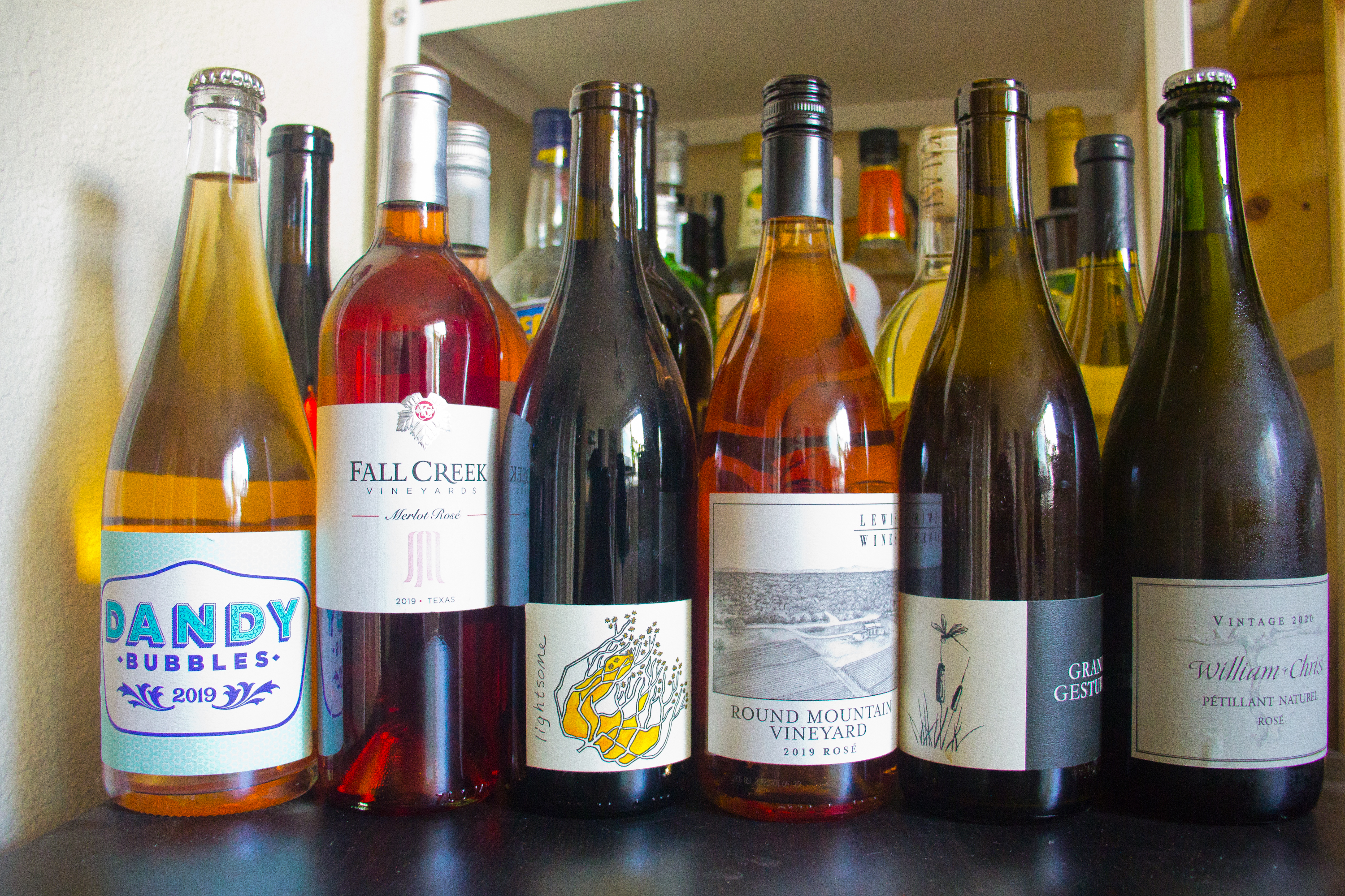 """A group of wine bottles ranging from rosés to whites to reds, with labels reading """"Dandy Rose,"""" """"Fall Creek Vineyards,"""" an abstract yellow-white-black image, """"Round Mountain Vineyard"""" and an image of a vineyard acre, an illustration of a weed and a flying insect, and """"William Chris Petillant Natural."""""""