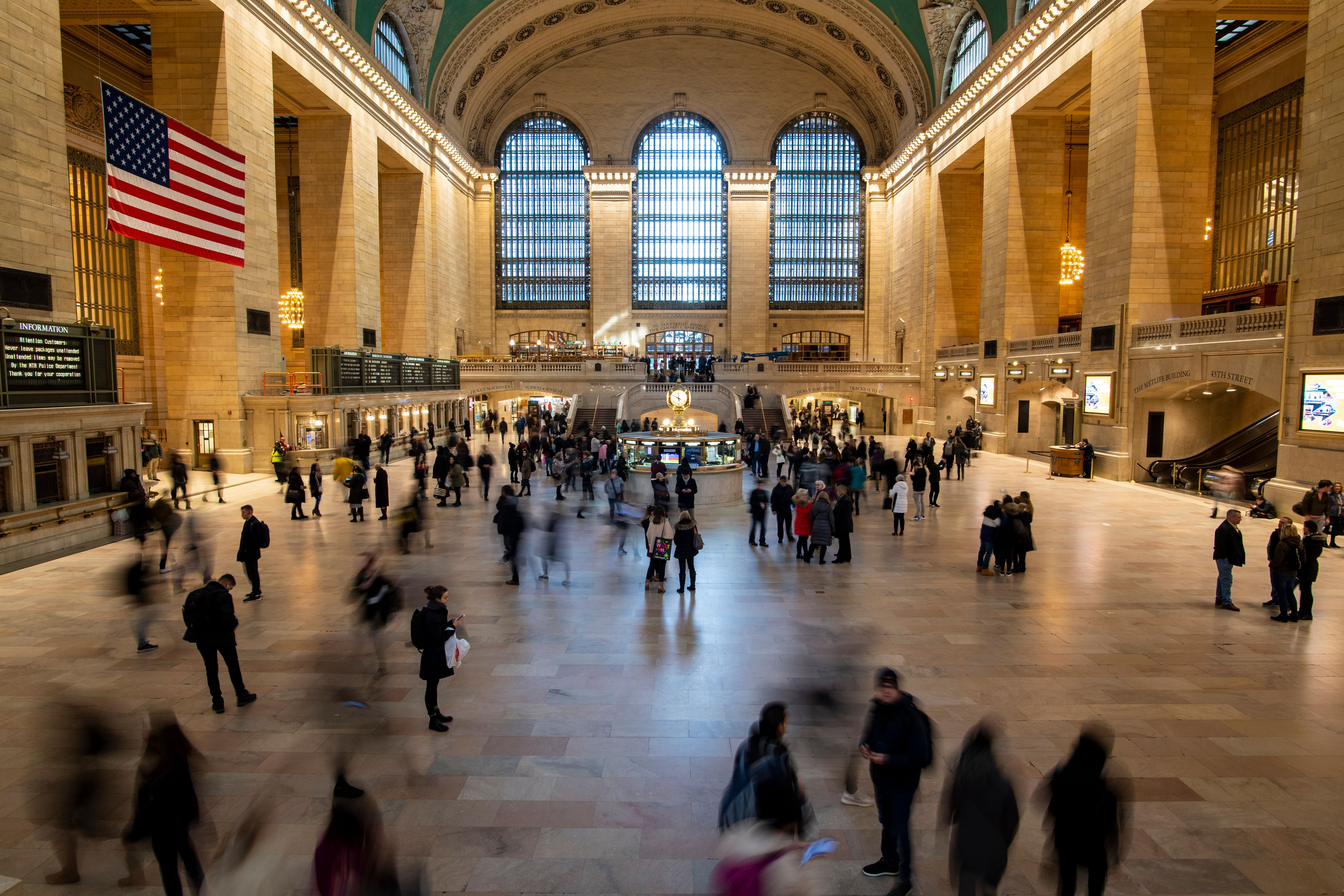A high-ceilinged interior of a train station with large windows and crowds of people walking across the main concourse. A large American flag hangs on the left wall.