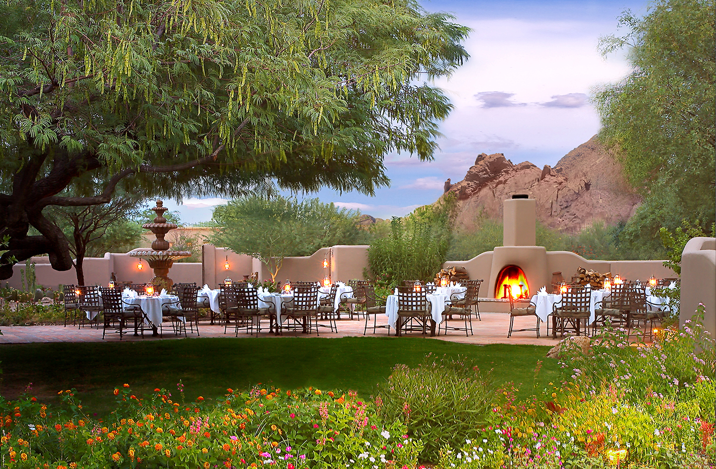 A photo looking out over a lush flower garden and lawn, past a tree, to a patio with tables set up beside a Pueblo-style fireplace with a fire roaring.