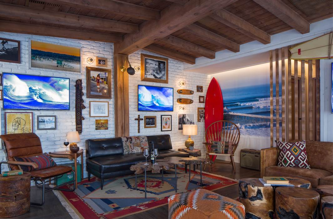 The lounge at Tower12 decorated with TVs, a surfboard, surf mural, and various pieces of art.