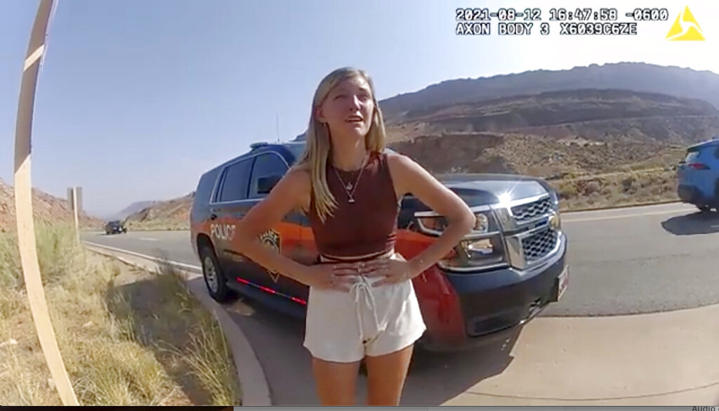 """Gabrielle """"Gabby"""" Petito talking to a police officer near the entrance to Arches National Park."""