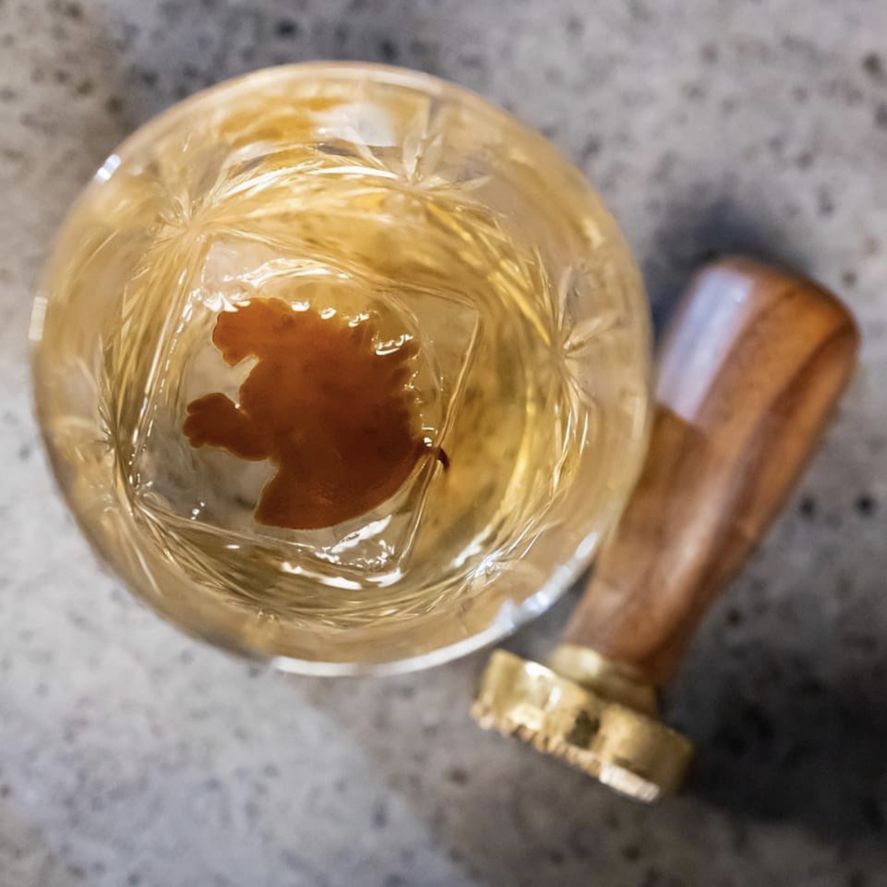 An amber colored cocktail with a letter seal stamper laying next to it