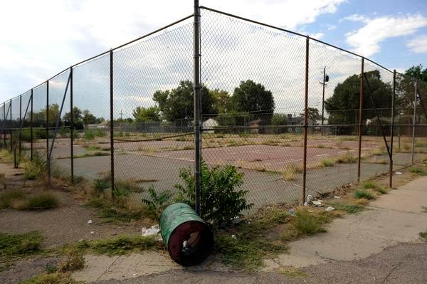 The corner of a chain link fence enclosing pavement and weeds at the former Adams City High School in Adams County, Colo.