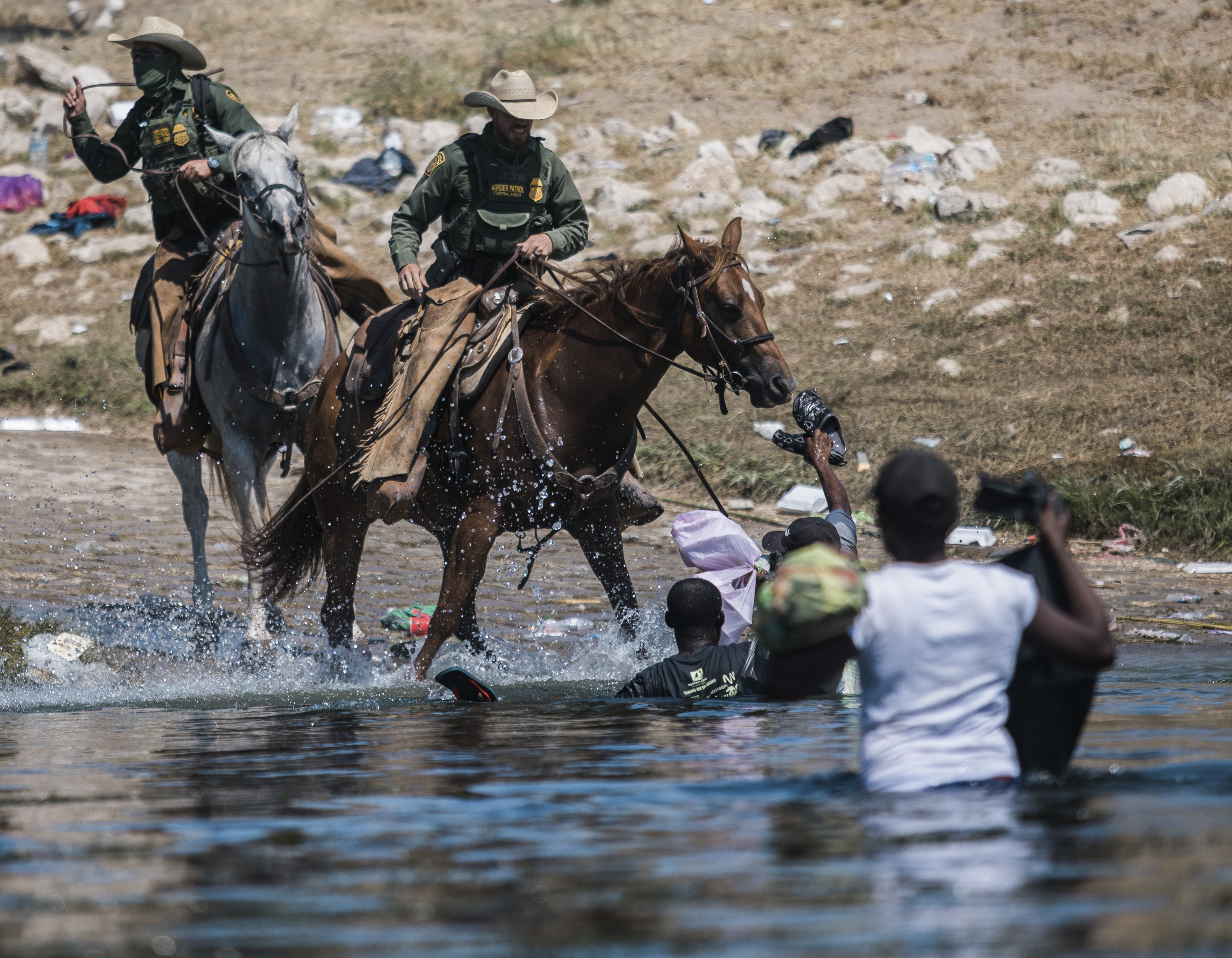 U.S. Customs and Border Protection mounted officers attempt to contain migrants as they cross the Rio Grande from Ciudad Acuña, Mexico, into Del Rio, Texas, Sunday, Sept. 19, 2021. Thousands of Haitian migrants have been arriving to Del Rio, Texas, as authorities attempt to close the border to stop the flow of migrants.