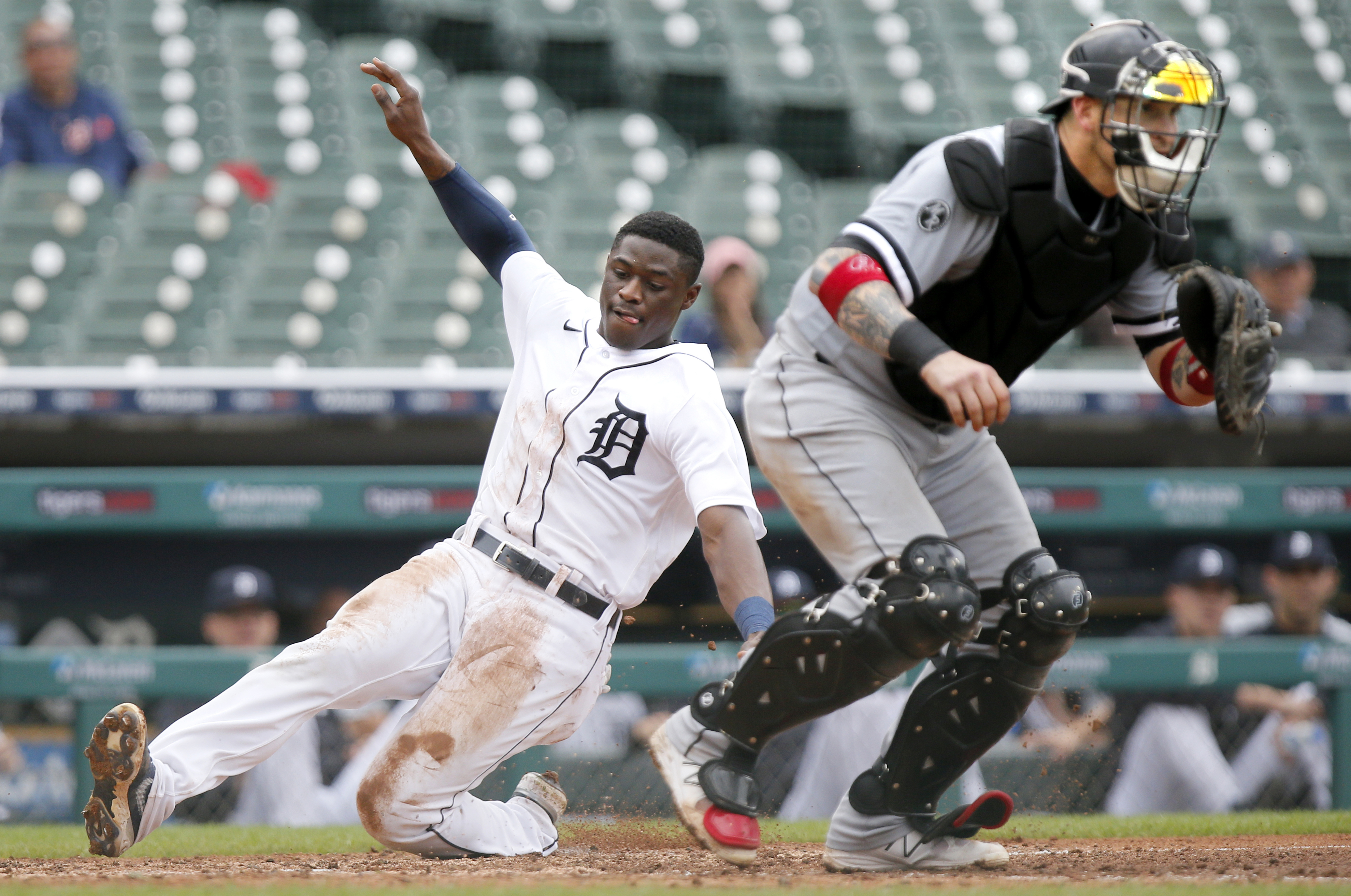 The Tigers' Daz Cameron scores behind White Sox catcher Yasmani Grandal during the fourth inning Tuesday.