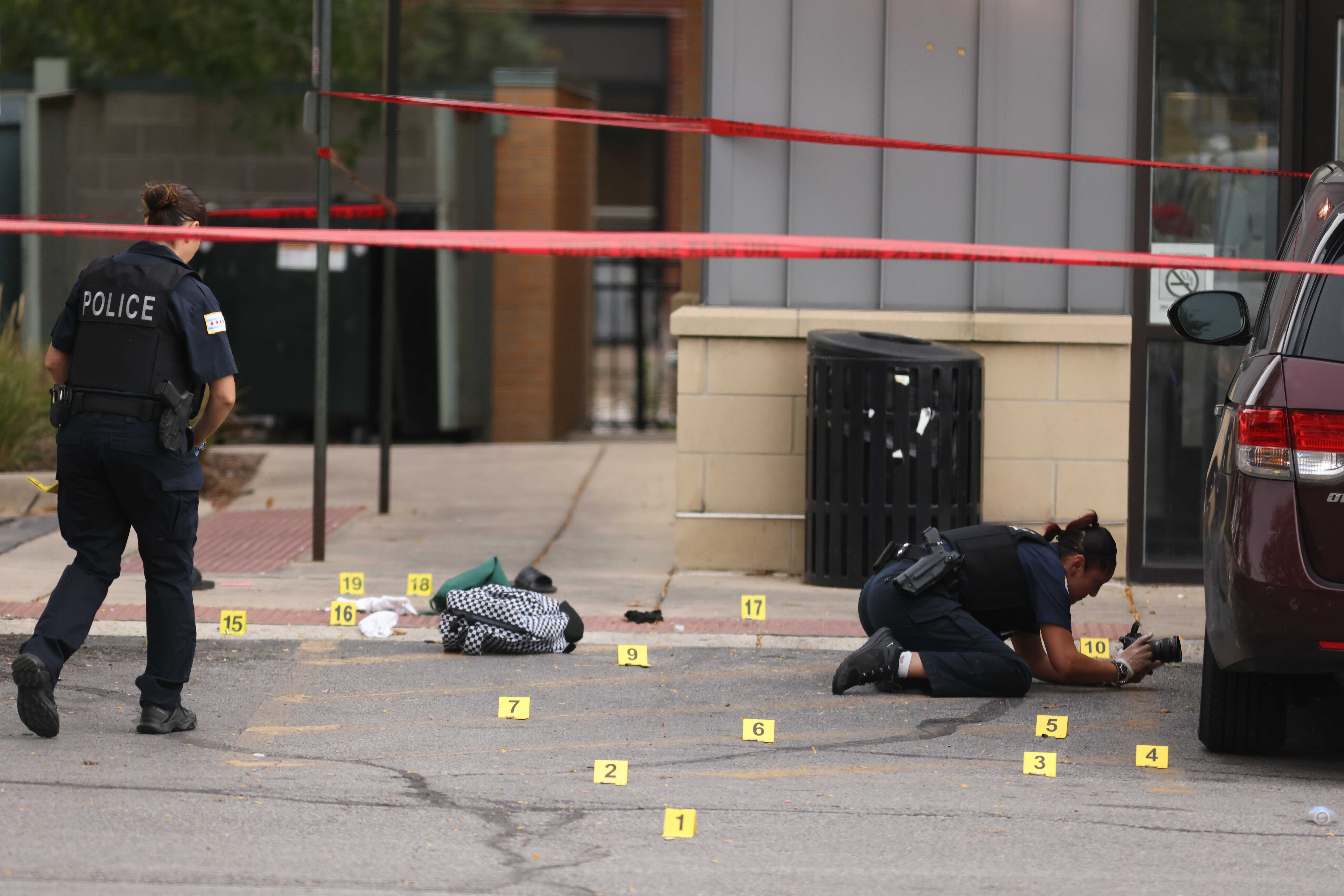 Chicago police officers investigate the scene of the fatal shooting of a 15-year-old student