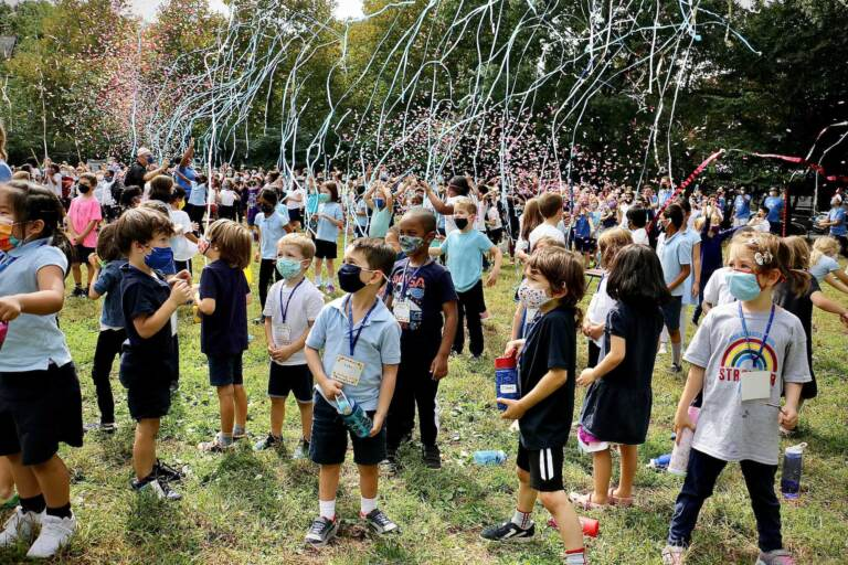 Students in masks celebrate outside at Penn Alexander after being announced as a National Blue Ribbon School. Streamers are in the air above the students.