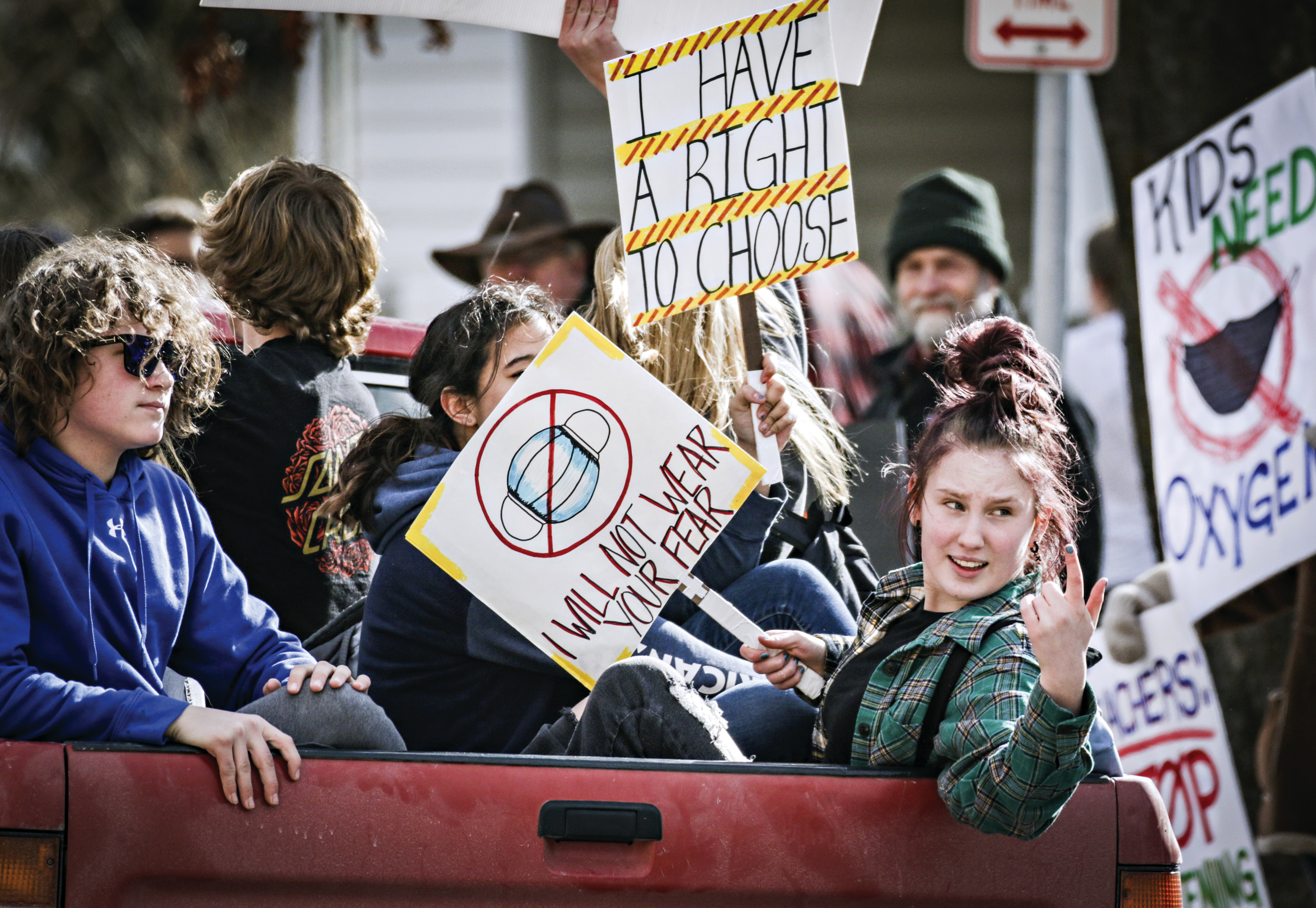 Students with signs ride in the back of a pickup truck to protest the Kalispell School District's face mask requirement.