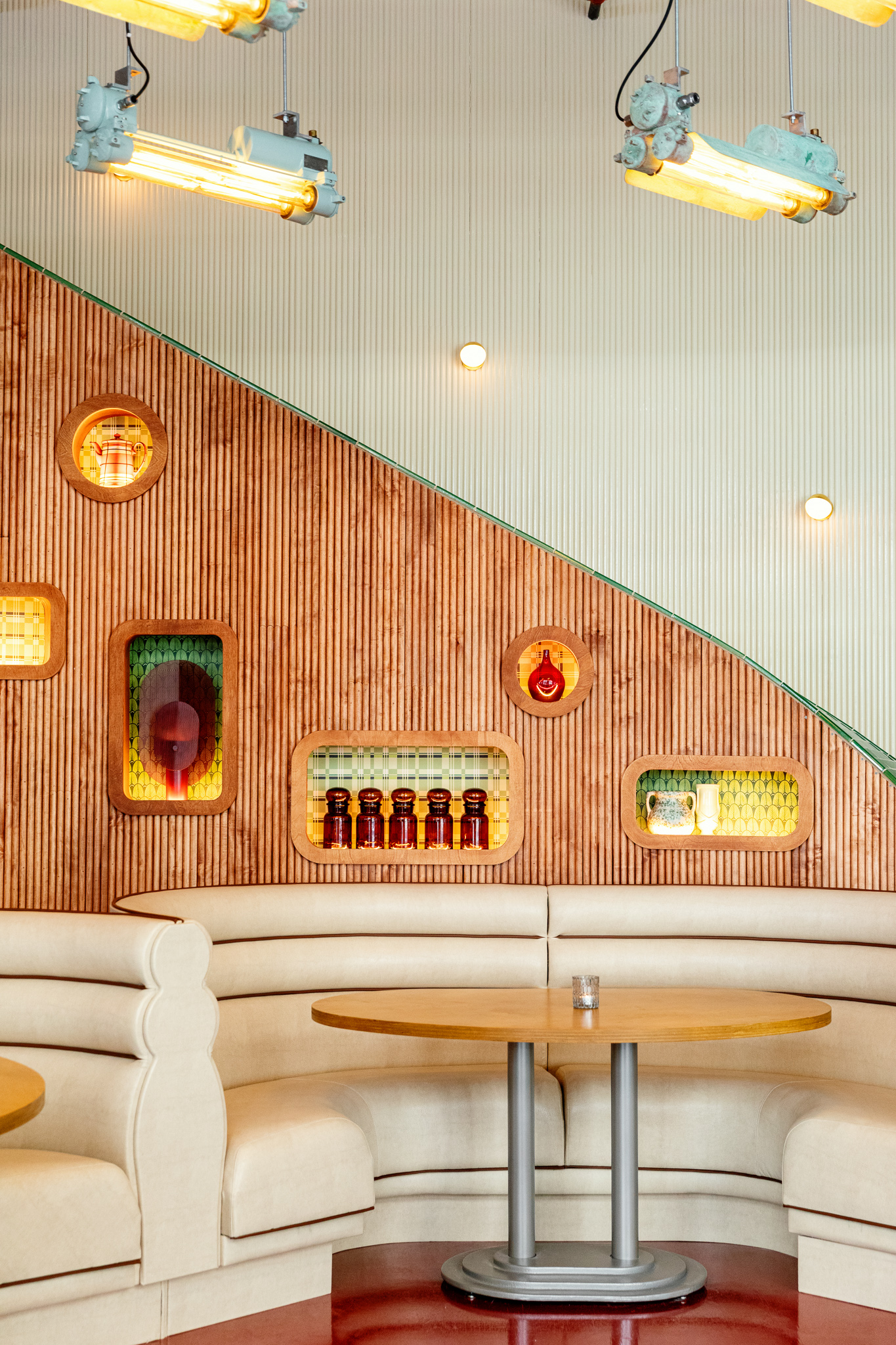 A wall behind a restaurant booth holds a clock, art and other knickknacks