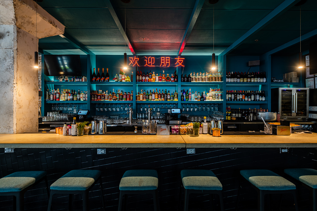 """The main bar at Bar Chinois has a neon with Chinese characters that spell out, """"Welcome friend."""""""