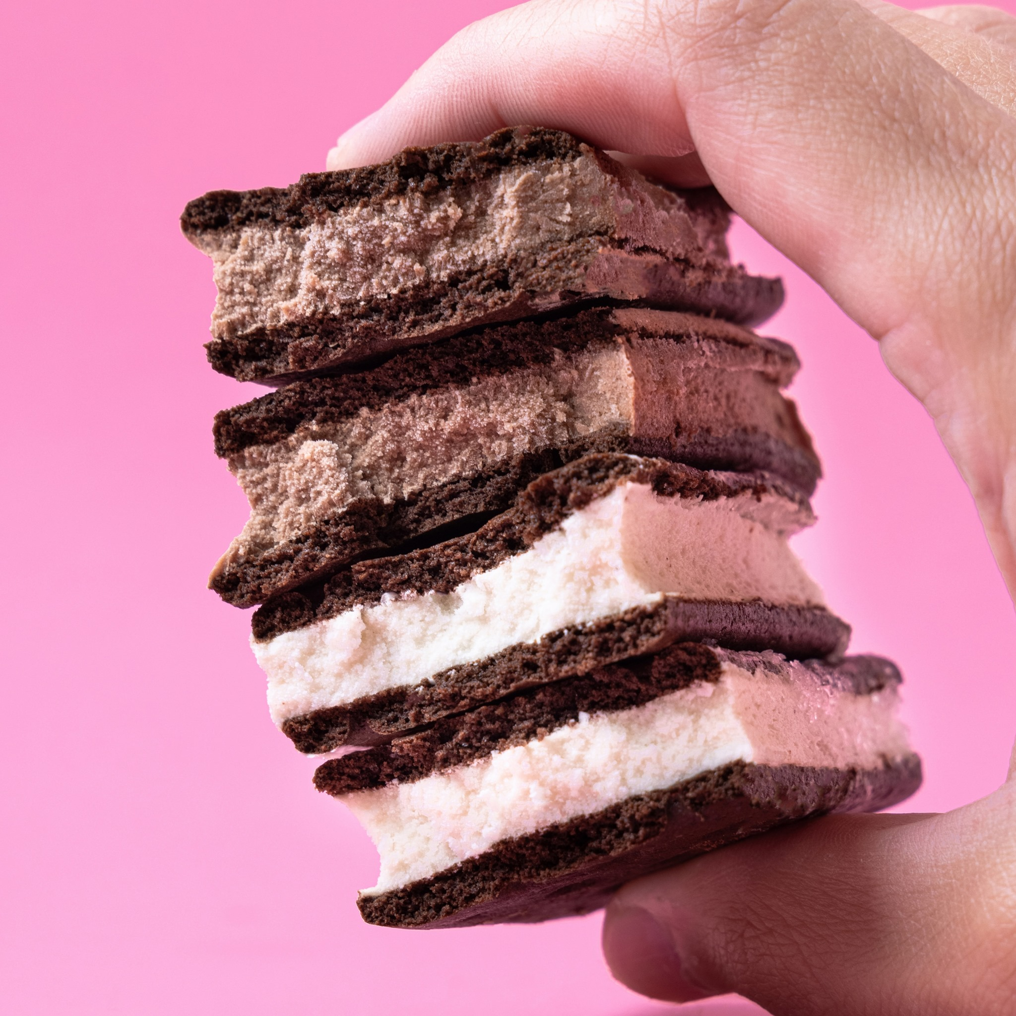 A hand holds ice cream sandwiches on a pink background.
