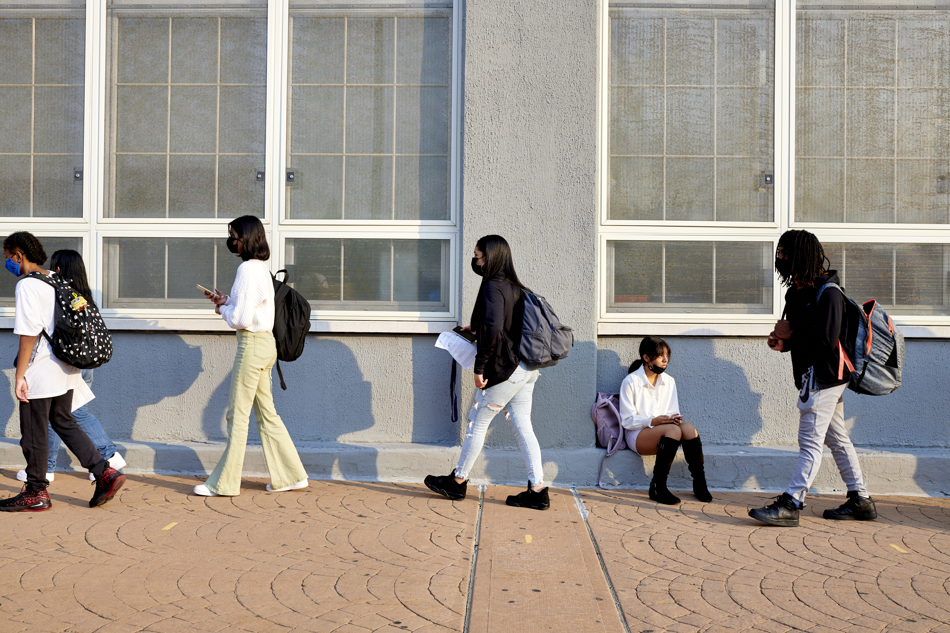 Students wait in line on school campus for COVID screening before classes begin.
