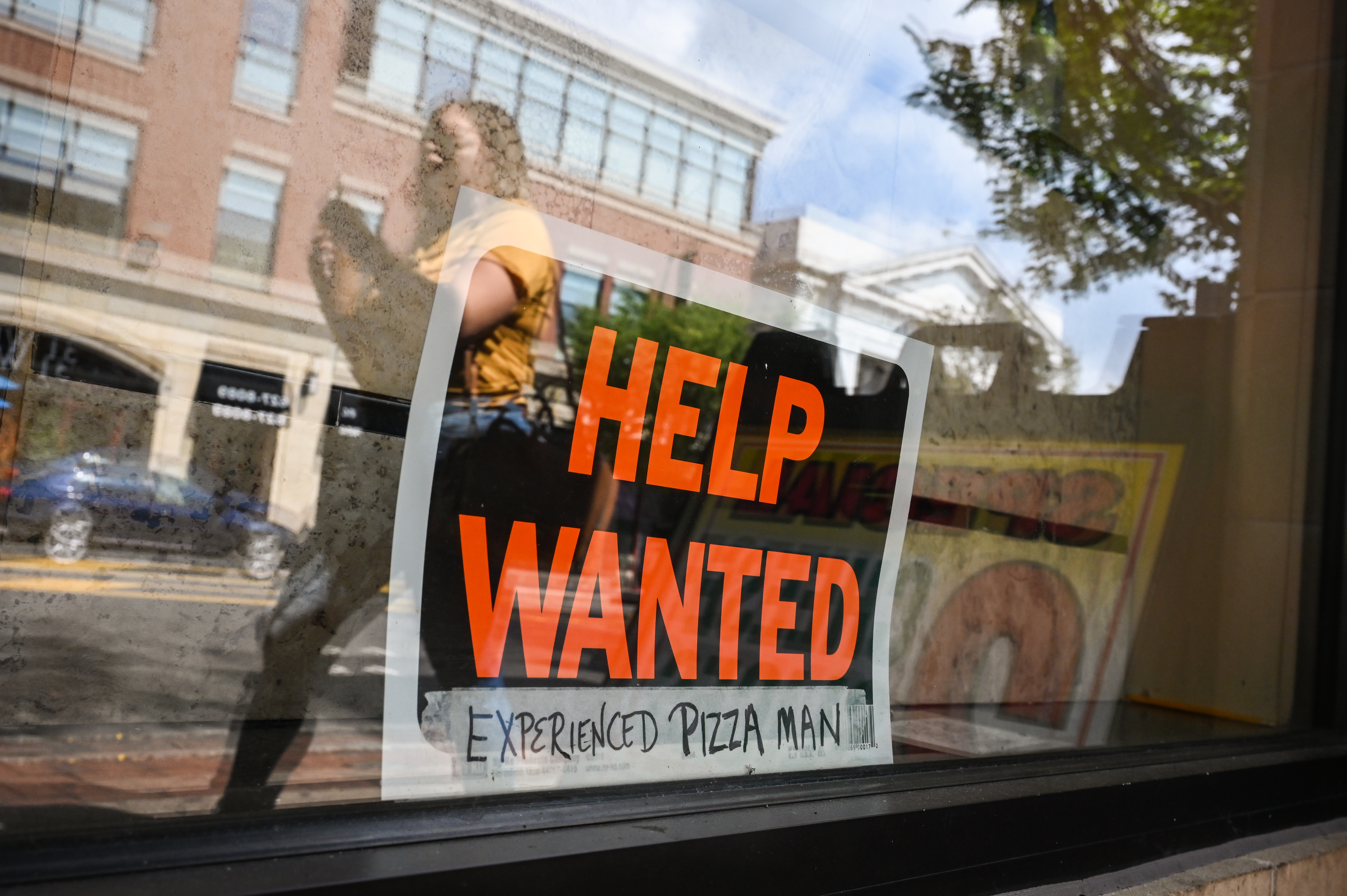 A help wanted sign in window of Long Island pizzeria