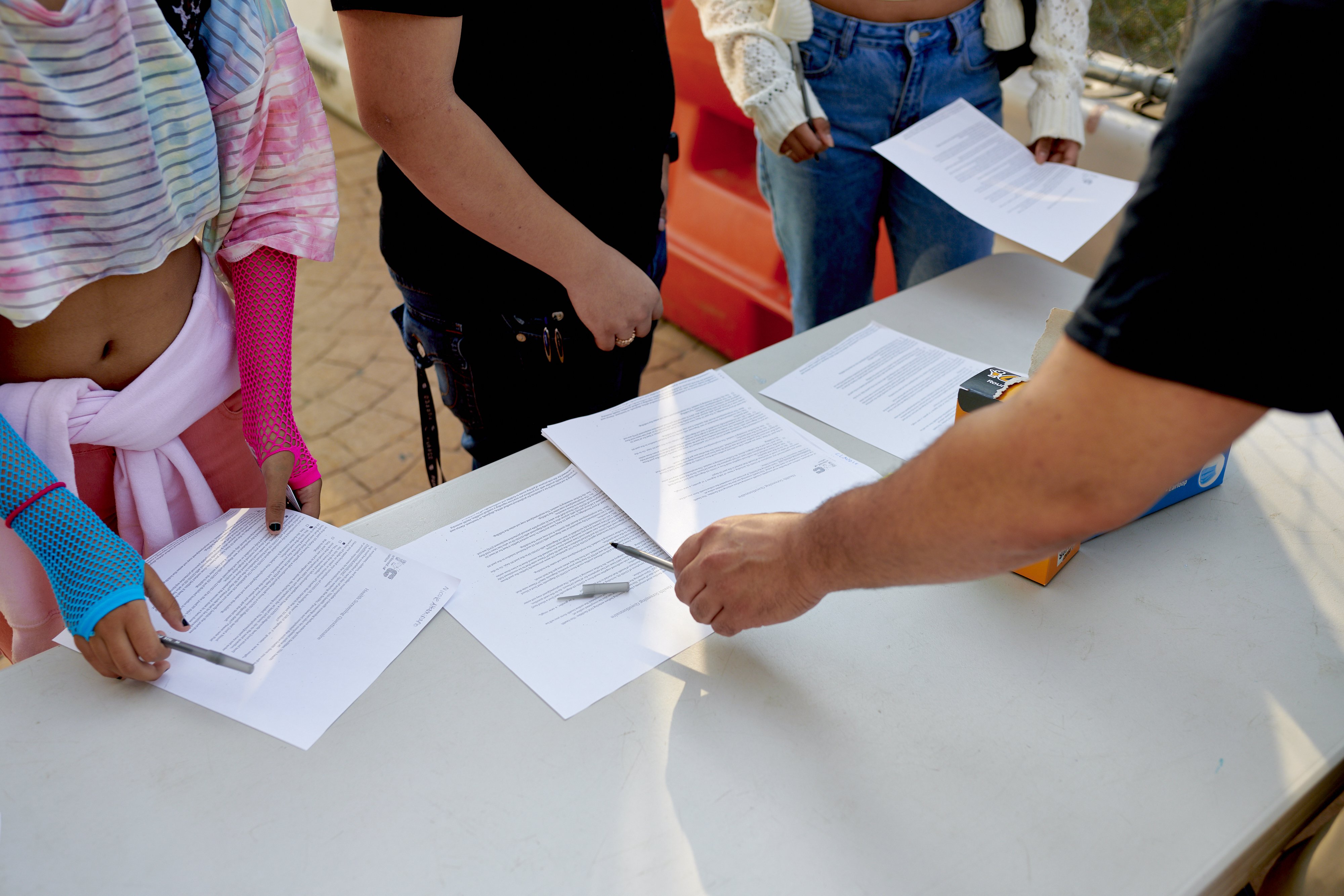 Students receive COVID screening forms and pens at a table from faculty.