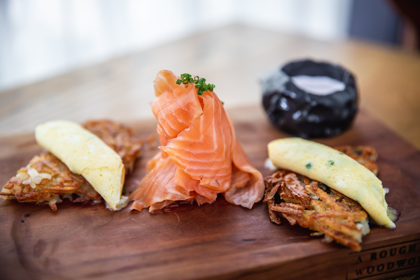 salmon, potato gateaux, and omelettes on a wooden board