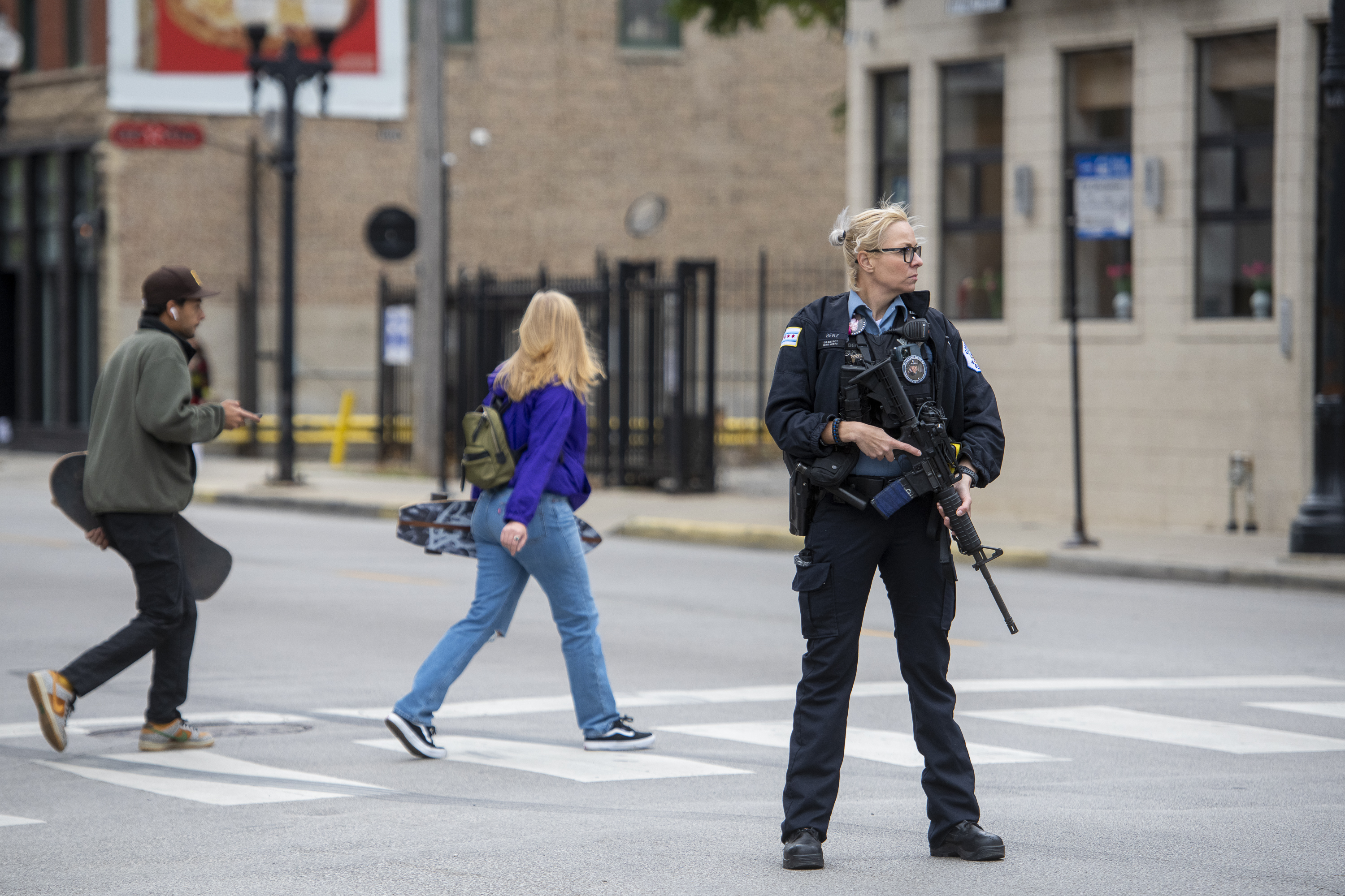 A Chicago police officer with a rifle helps direct traffic after a SWAT incident in the 200 block of West Division Street, in the Old Town neighborhood, Wednesday, Sept. 22, 2021. The initial call that prompted the SWAT response was found to be fake.