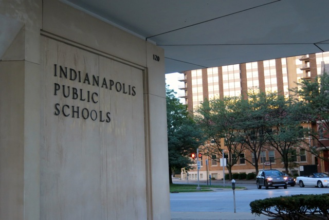 The facade of the Indianapolis Public Schools building, with a street and building in the background.