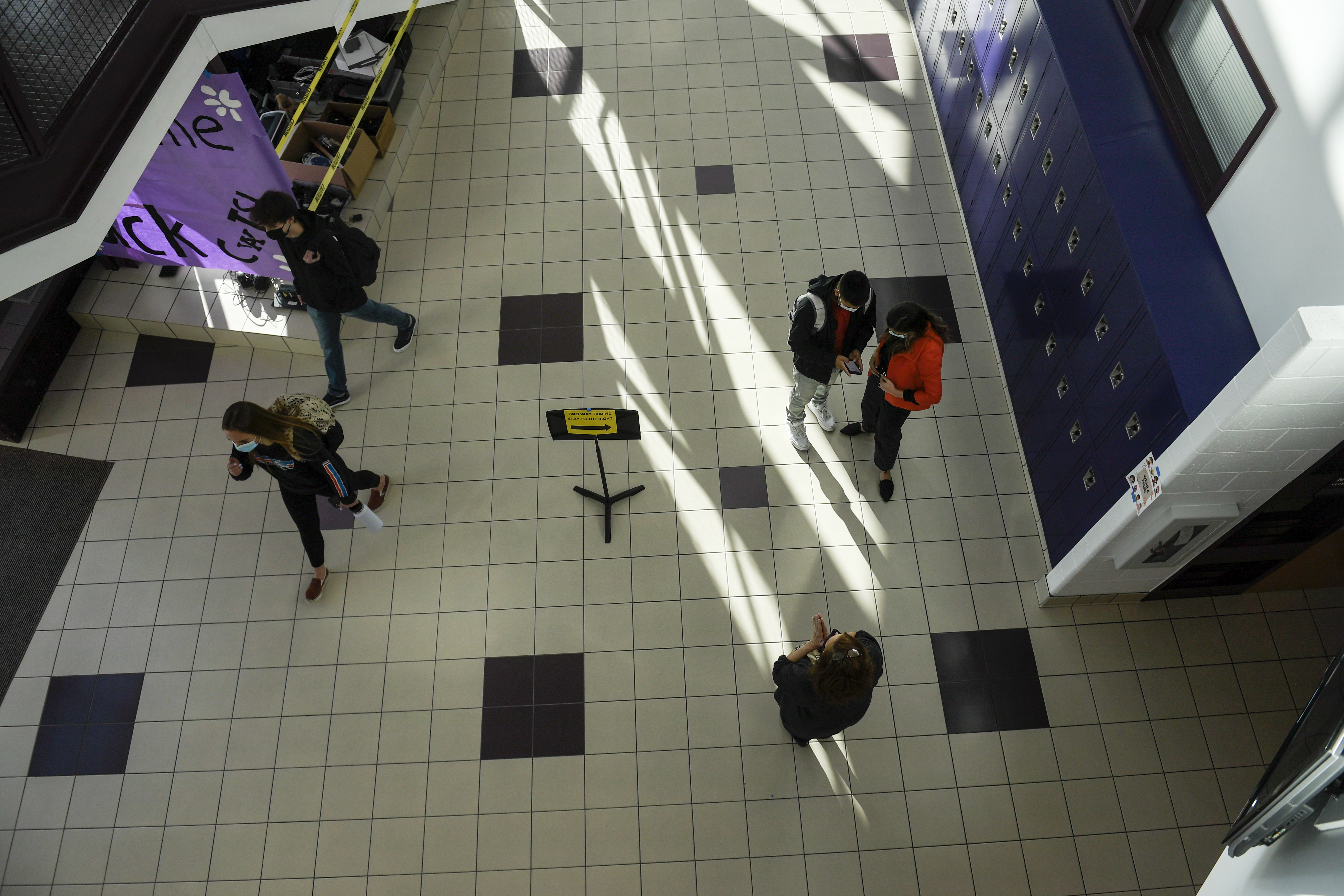 Seen from above, small groups of masked students walk in a wide school hallway.