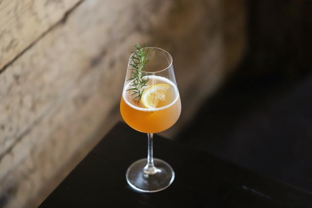 A wine glass filled with orange cocktail garnished with a sprig of rosemary and lemon.