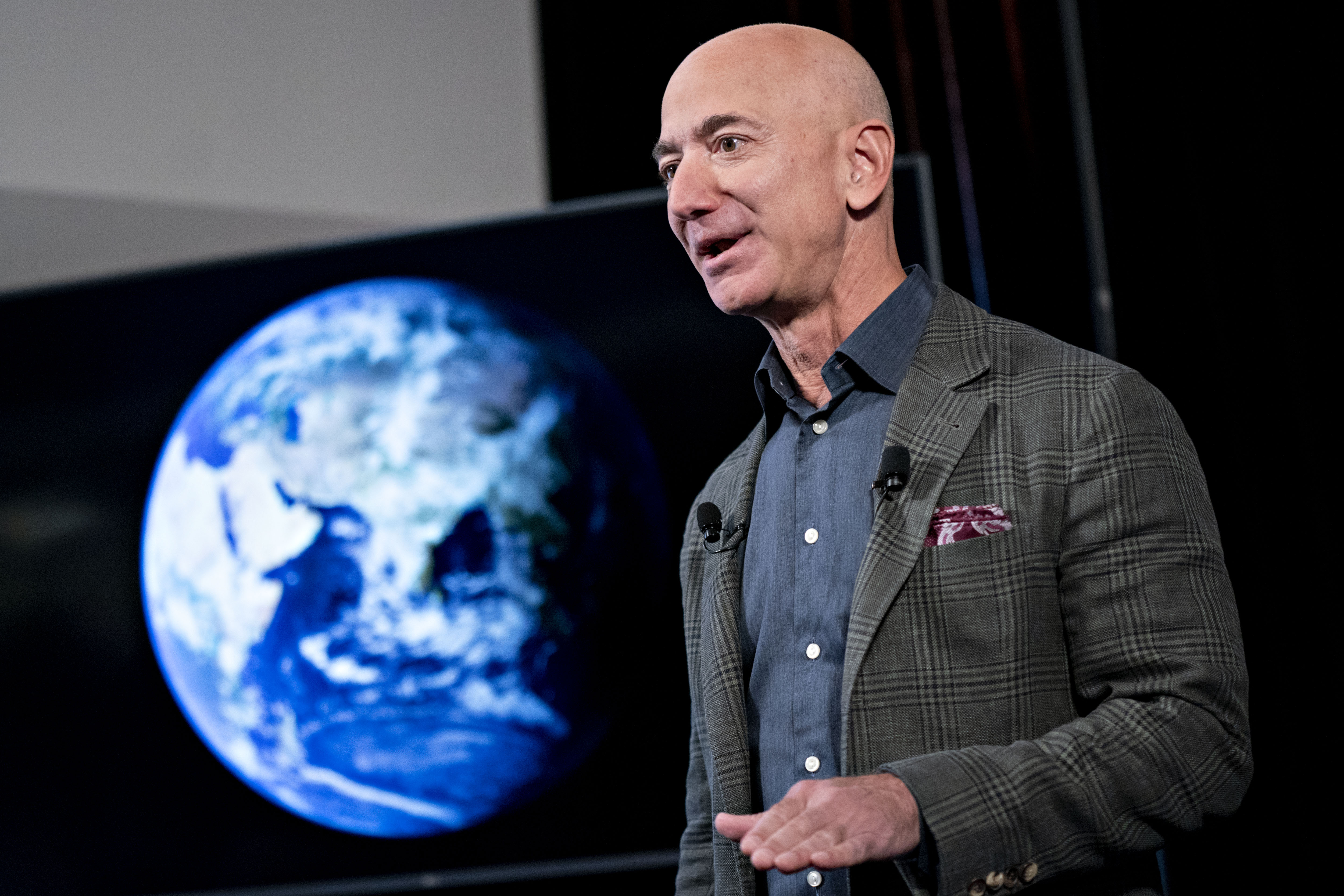 Jeff Bezos speaking onstage in front of a screen showing a picture of the Earth as seen from space.