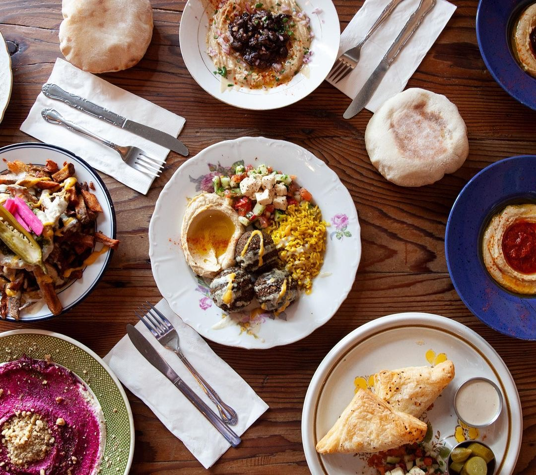 A photo of a spread of a vegan dishes at Aviv, including hummus, falafel, bourekas, and shawarma fries