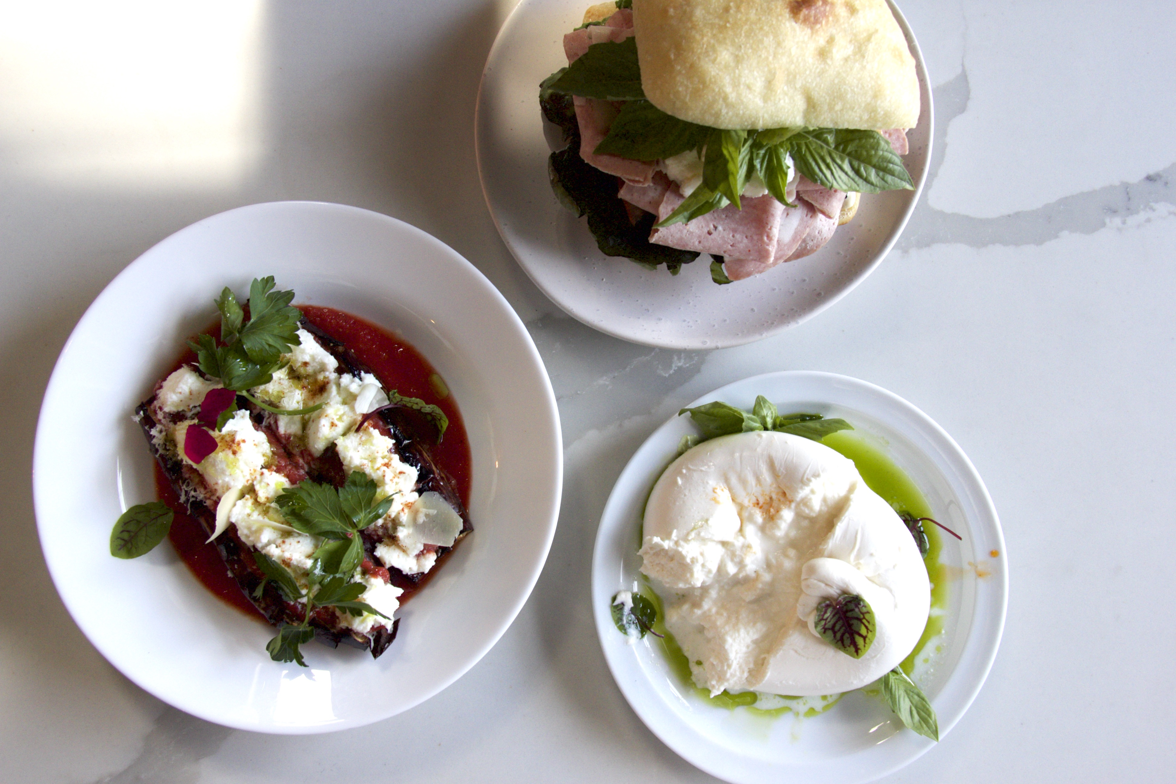 three dishes with burrata and sandwich on marble table