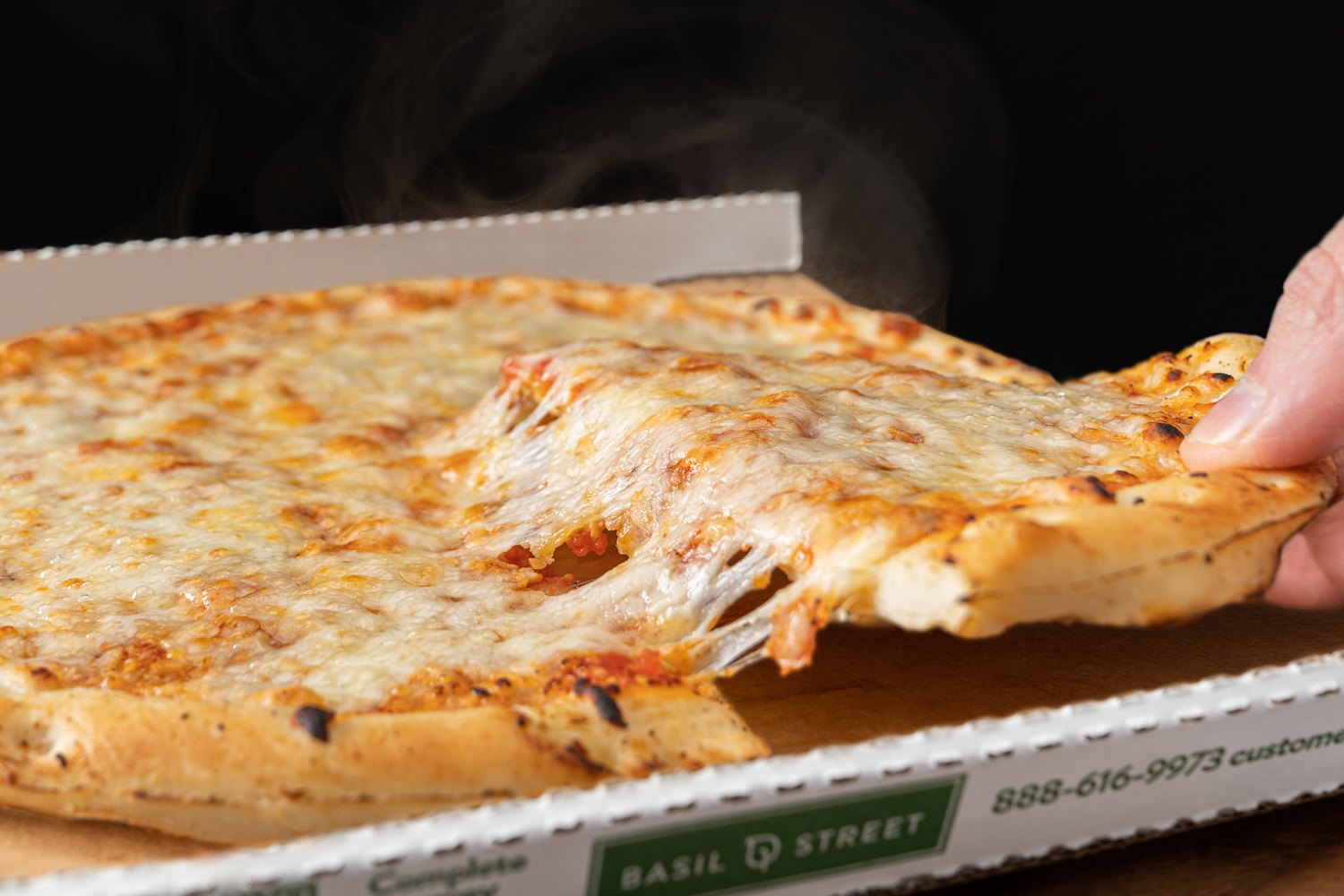 A cheese pizza in a cardboard box with cheese pull