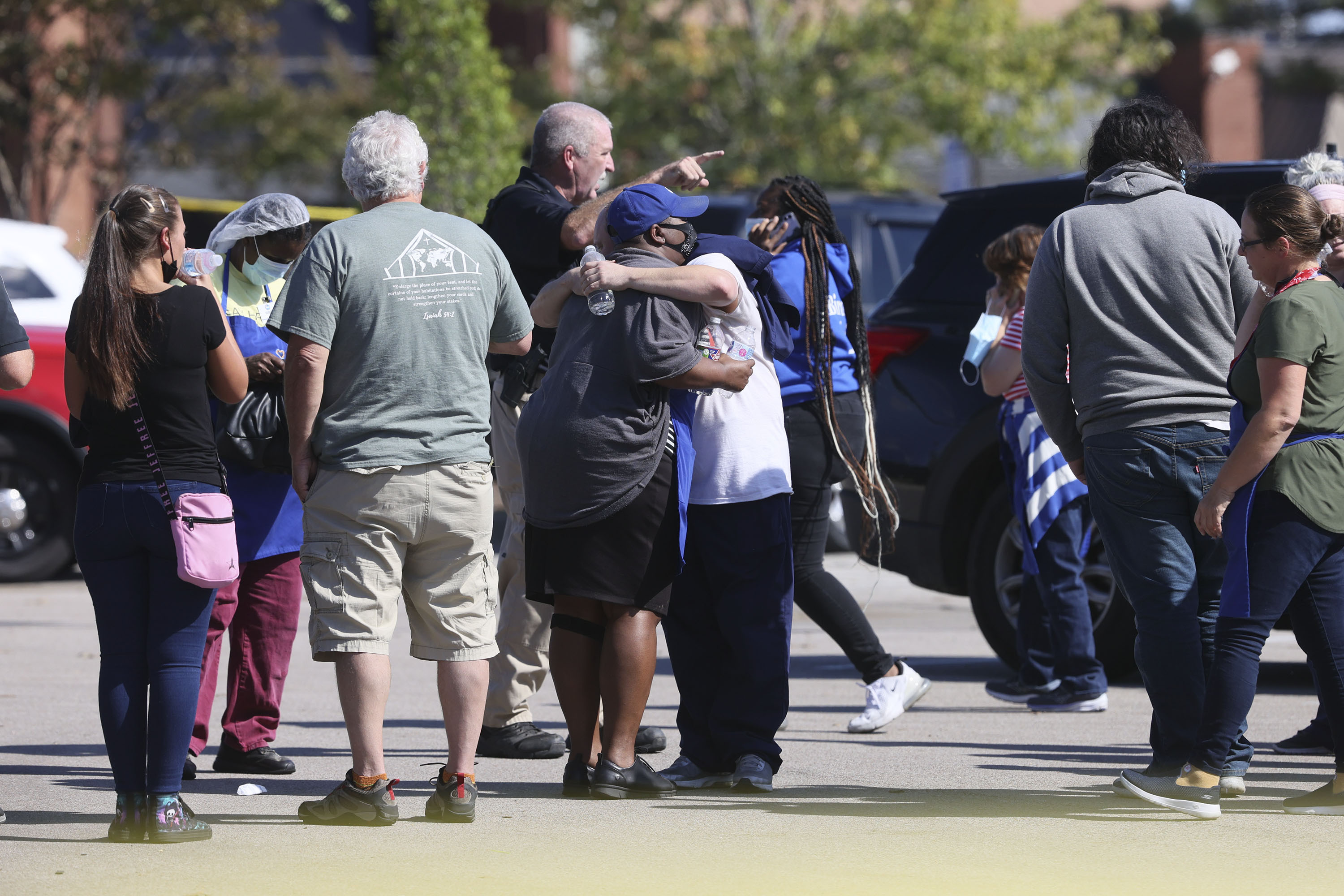 People embrace as police respond to the scene of a shooting at a Kroger's grocery store in Collierville, Tenn., on Thursday, Sept. 23, 2021.