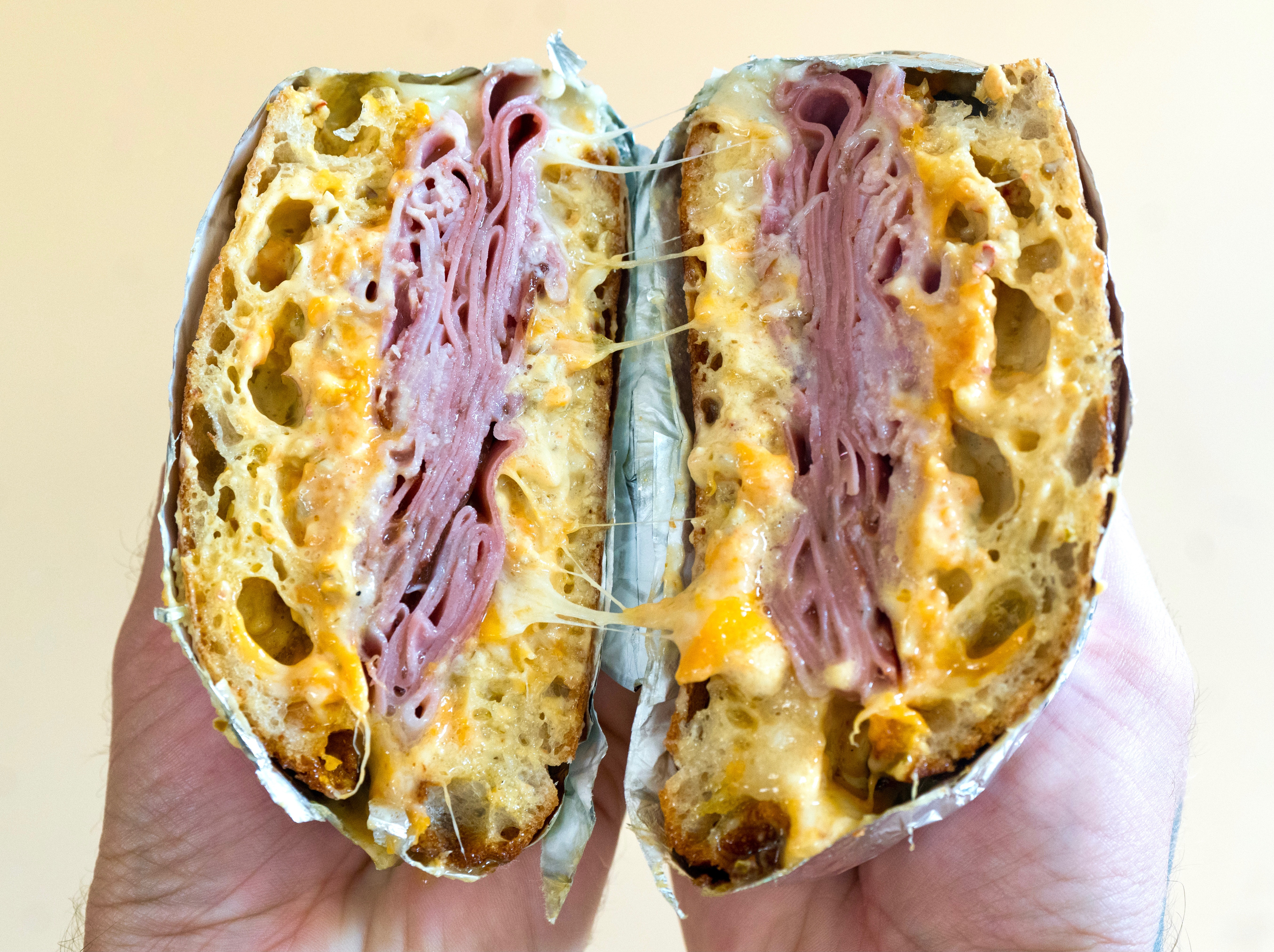 A sandwich that is cut in half with layers of melty cheese and sliced pink meat